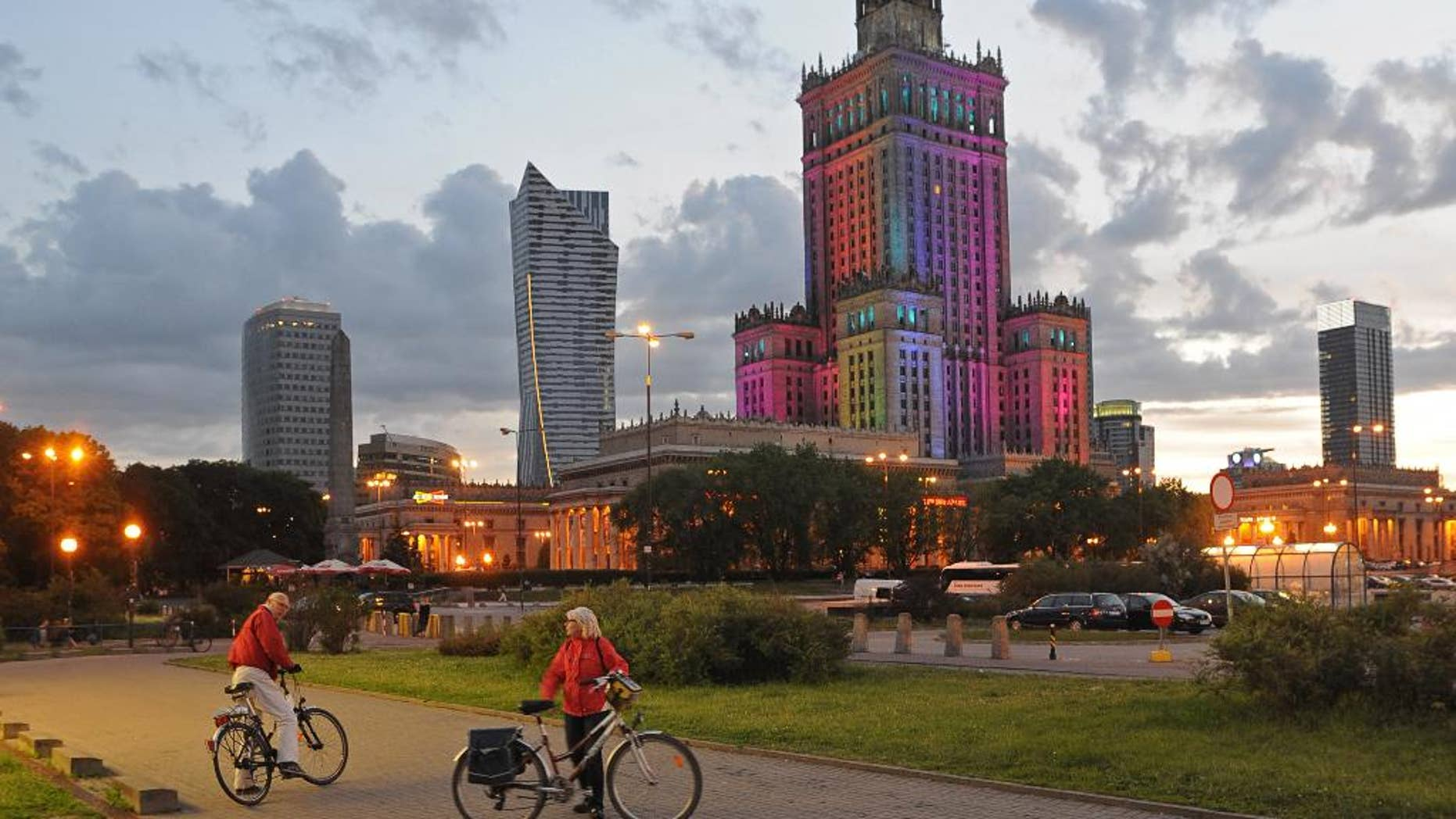 The communist era Palace of Culture, colorfully illuminated, is surrounded by modern skyscrapers, in Warsaw, Poland, Saturday, May 31, 2014. (AP Photo/Alik Keplicz)