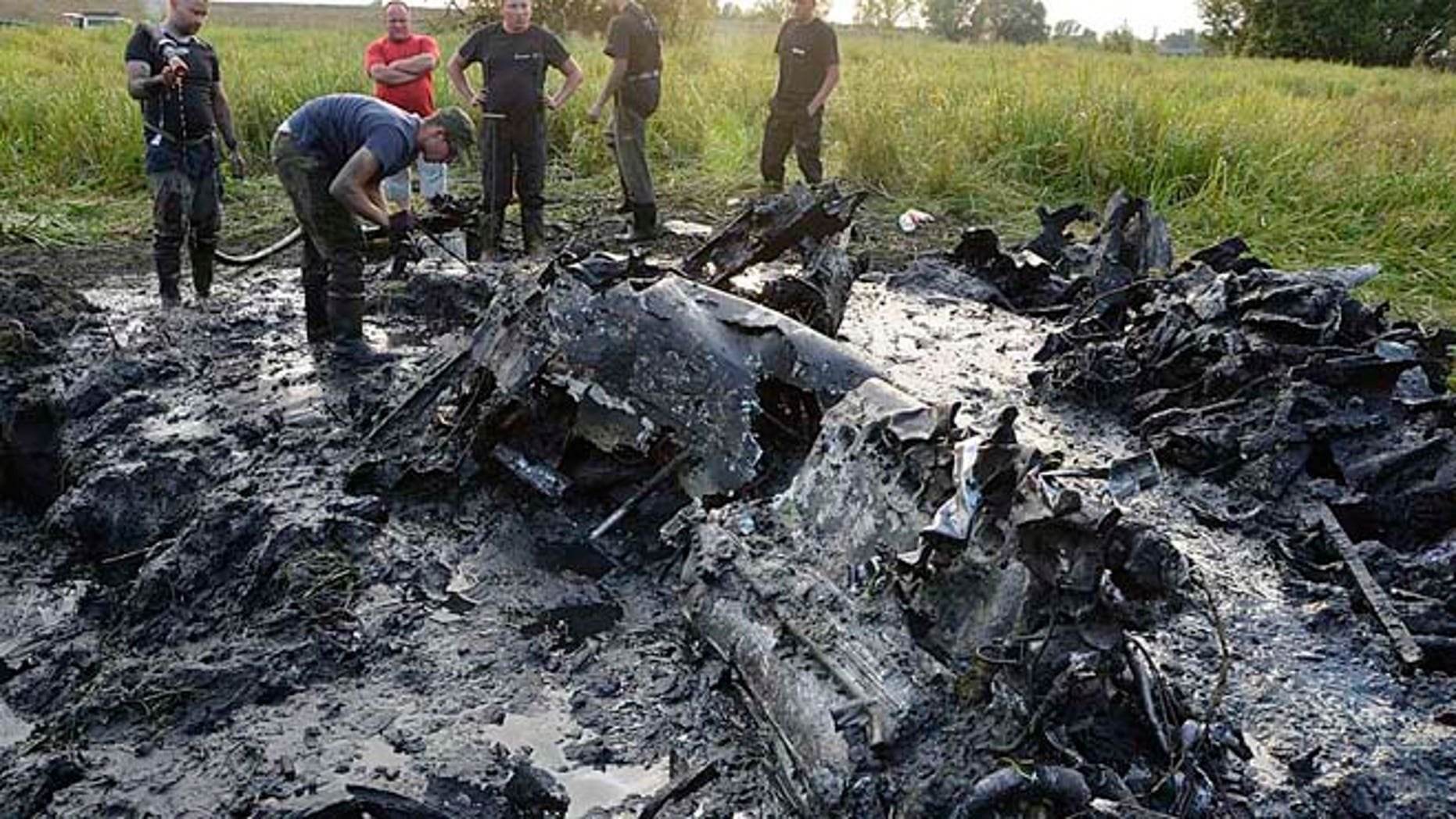 Aug. 23, 2015: Firefighters are retrieving the remains of a Soviet WW II fighter-bomber plane from muddy riverbed near Wyszogrod, Poland.
