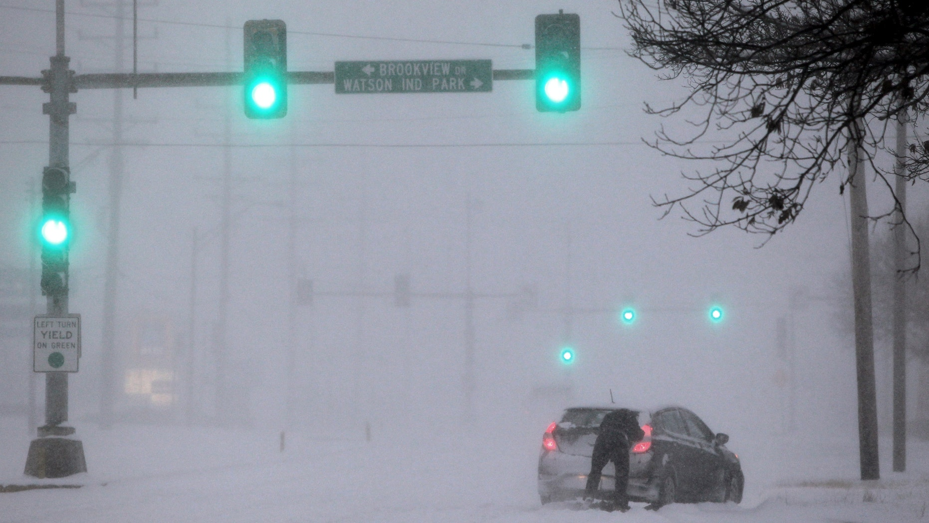 "A Crestwood motorist tries to get his car moving along Watson Road in St. Louis as heavy snow falls on Sunday, Jan. 5, 2014. Snow-covered roads, high winds and ice were creating dangerous driving conditions from Missouri to Delaware on Sunday ahead of a ""polar vortex"" that'll bring below-zero temperatures not seen in years to much of the nation in the coming days, likely setting records. (AP Photo/St. Louis Post-Dispatch, Robert Cohen)  EDWARDSVILLE INTELLIGENCER OUT; THE ALTON TELEGRAPH OUT"