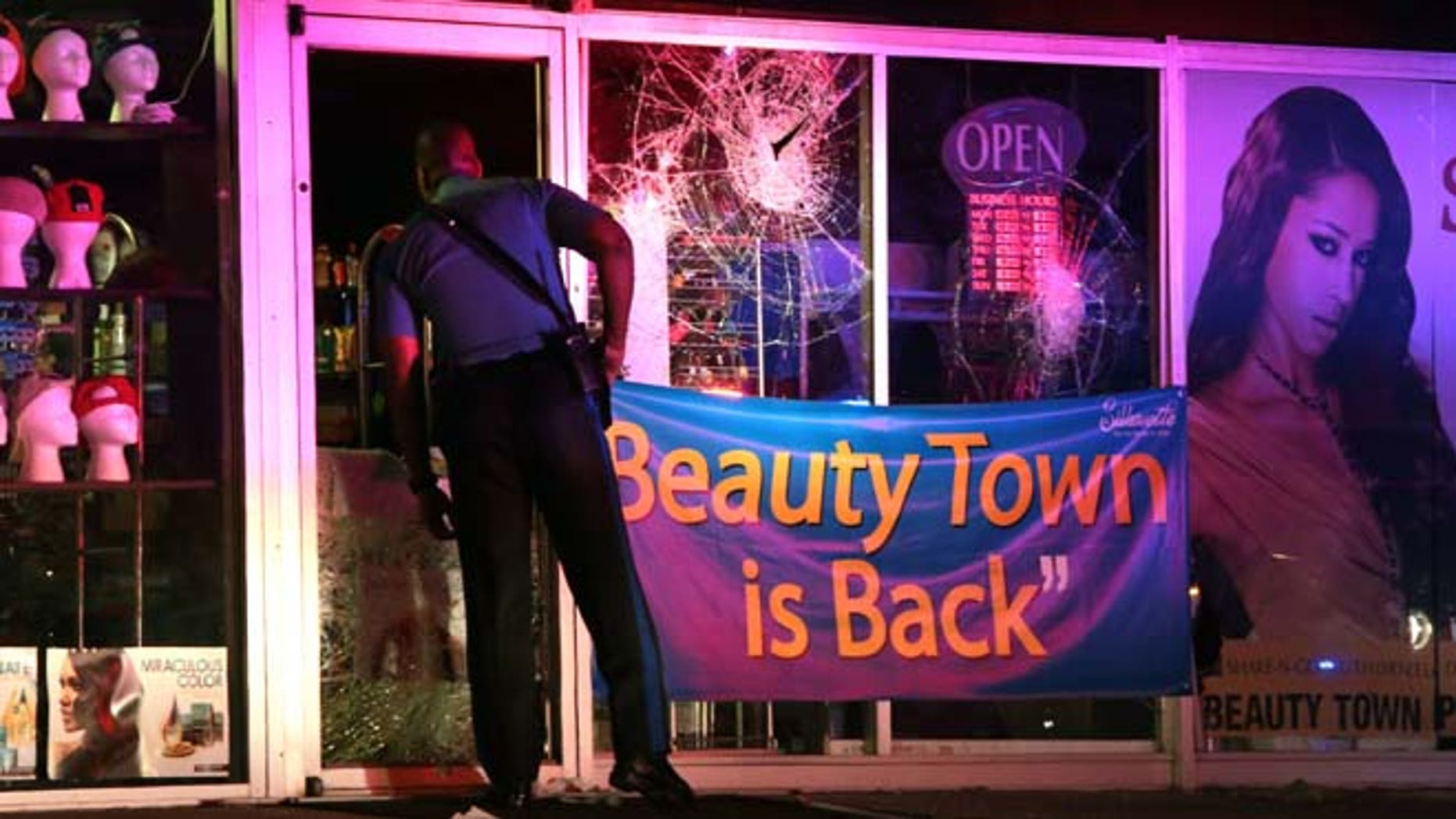 Sept. 23, 2014: A Missouri Highway Patrol trooper looks inside the vandalized Beauty Town store on West Florissant Avenue in Ferguson. (AP Photo/St. Louis Post-Dispatch)