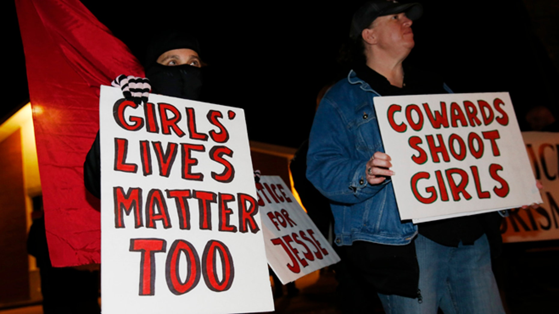 Nazzi McDonnell, left, of Colorado Springs, Colo., joins other participants in waving placards during a vigil near the scene of the early morning fatal shooting of a young woman who hit and injured a Denver Police Department officer while driving a stolen vehicle Monday, Jan. 26, 2015, in northeast Denver. (AP Photo/David Zalubowski)