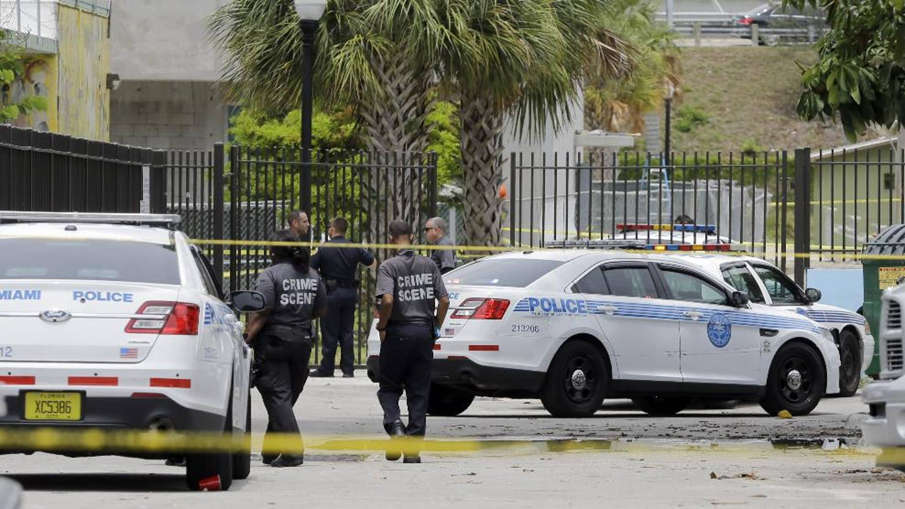 Miami Police officers at the scene where a man holding a pipe has been shot by a Miami police officer in a downtown park ,Thursday, June 11, 2015, in Miami. The man's condition and identity were not immediately available. He was taken to a local hospital for treatment. (AP Photo/Alan Diaz)
