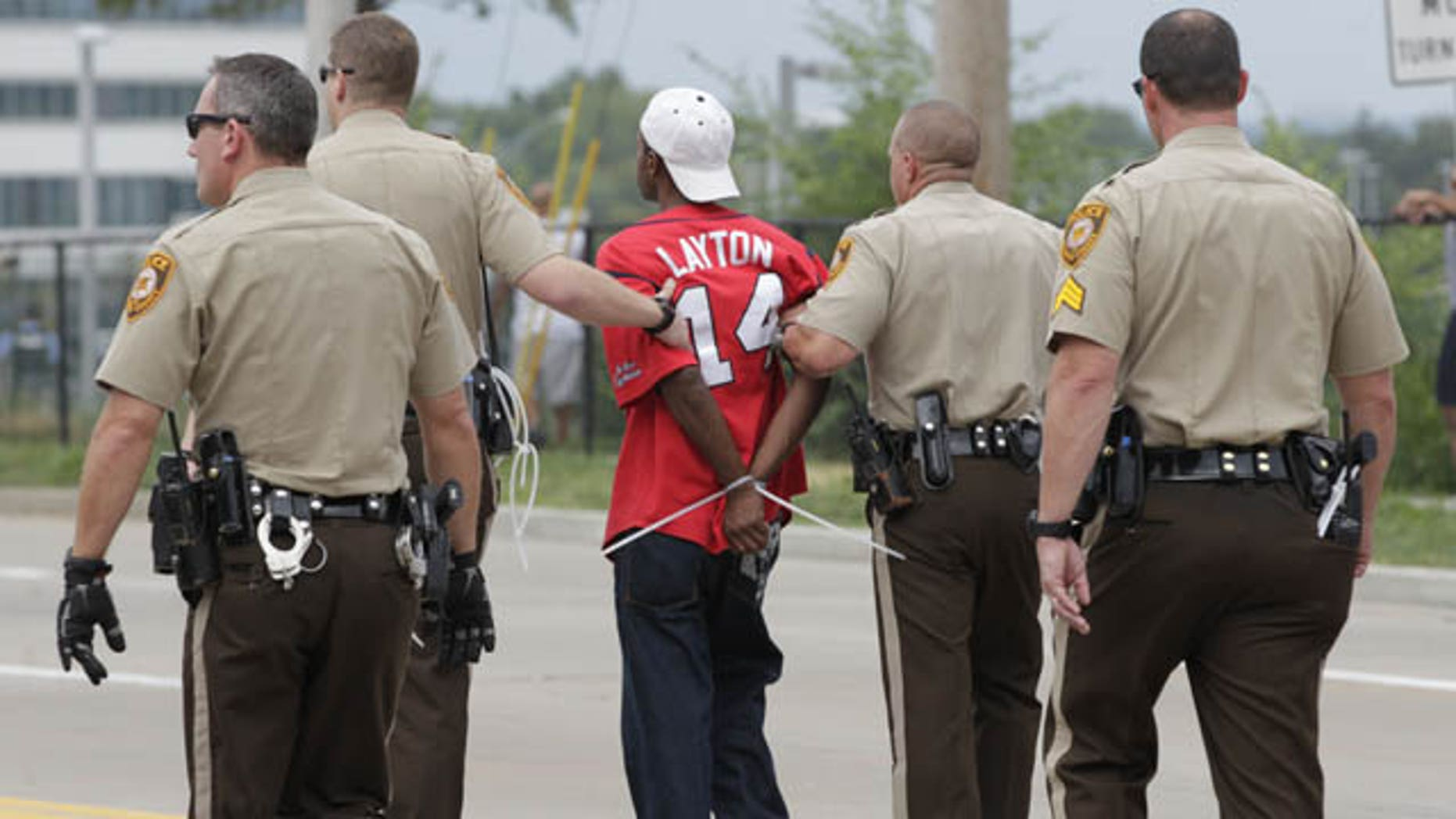 September 10, 2014: Police arrest a protester after he refused to leave the area of a protest aimed at shutting down Interstate 70 in Berkeley, Mo., near the St. Louis suburb of Ferguson, Mo. where Michael Brown, an unarmed, black 18-year old was shot and killed by a white police officer on Aug. 9. (AP Photo/Tom Gannam)