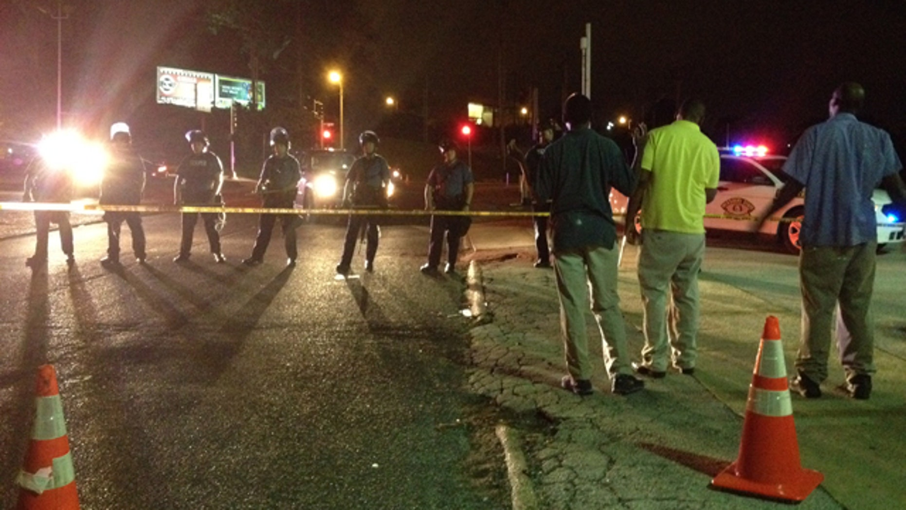 August 11, 2014: In this image made with a mobile phone, riot police line up in Ferguson, Mo. Authorities say more than 30 people have been arrested in Ferguson, where crowds have looted and burned stores, vandalized vehicles and taunted police after a vigil for an unarmed black man who was killed by police. (AP Photo/Jeff Roberson)