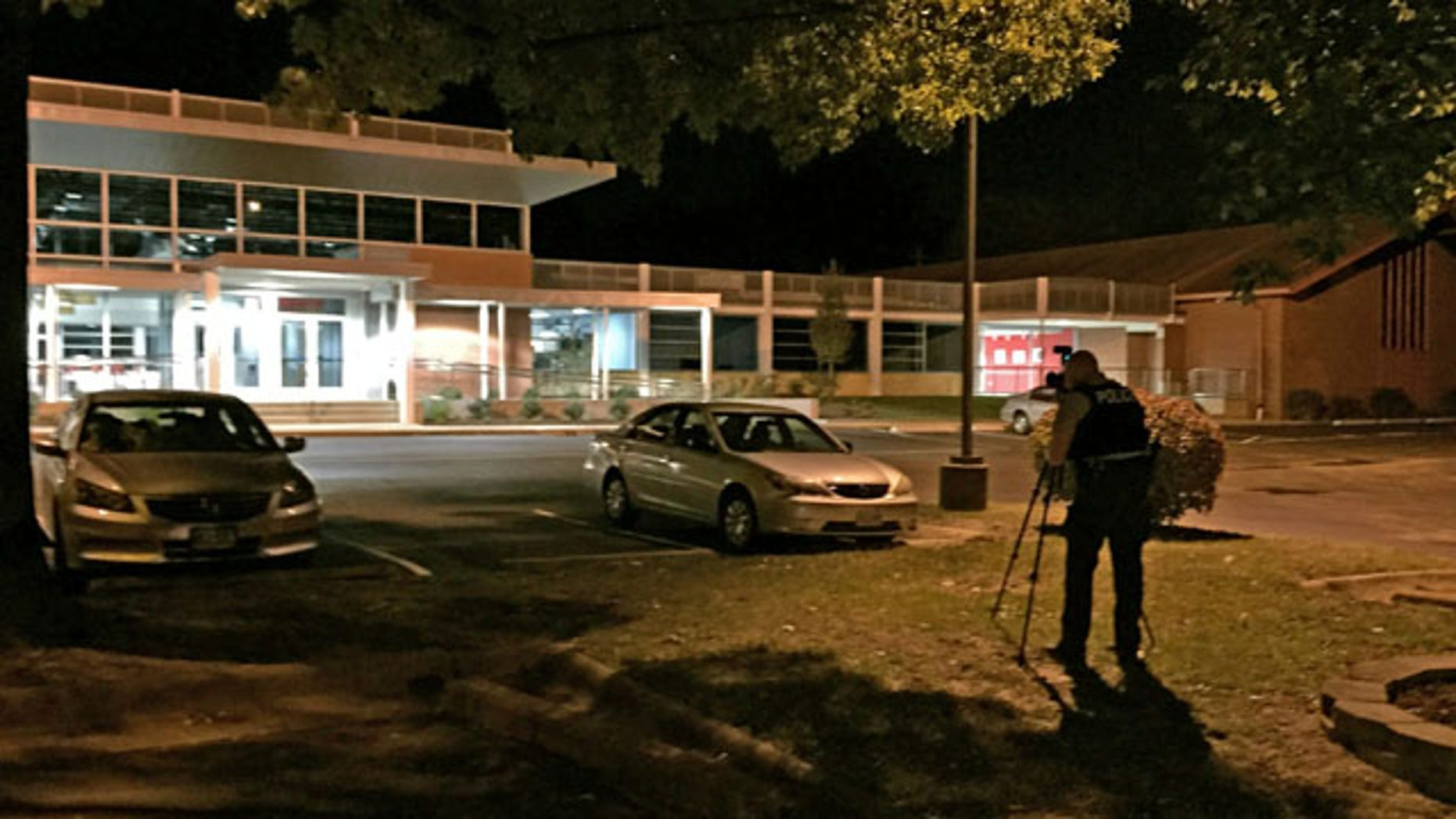 September 27, 2014: A police officer takes pictures outside the Ferguson Community Center in Ferguson, Mo. (AP Photo/St. Louis Post-Dispatch, Huy Mach).