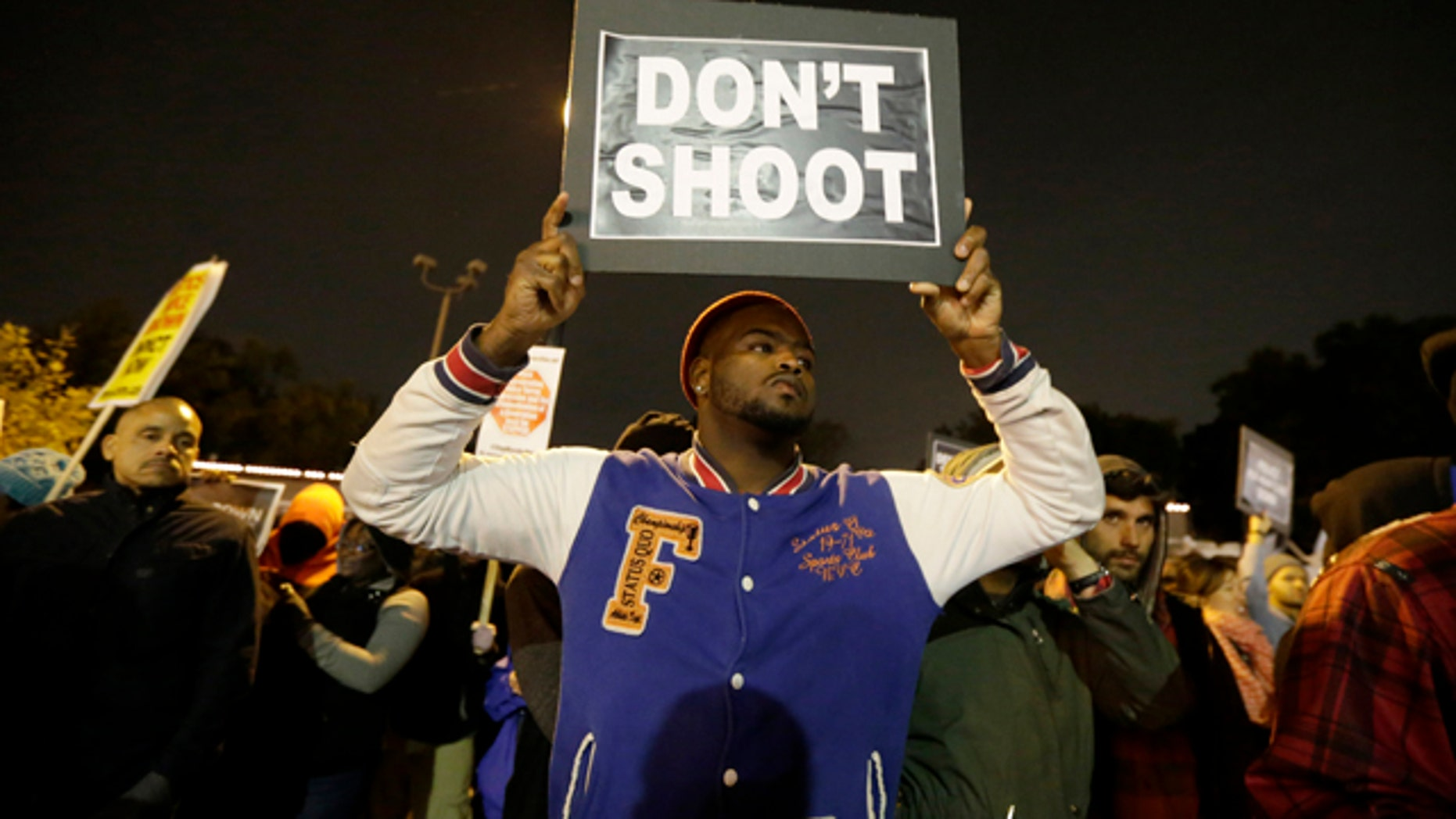 October 10, 2014: Protesters gather across the street from the Ferguson, Mo., police station in a continuing protest of the shooting of Michael Brown. (AP Photo/Charles Rex Arbogast)