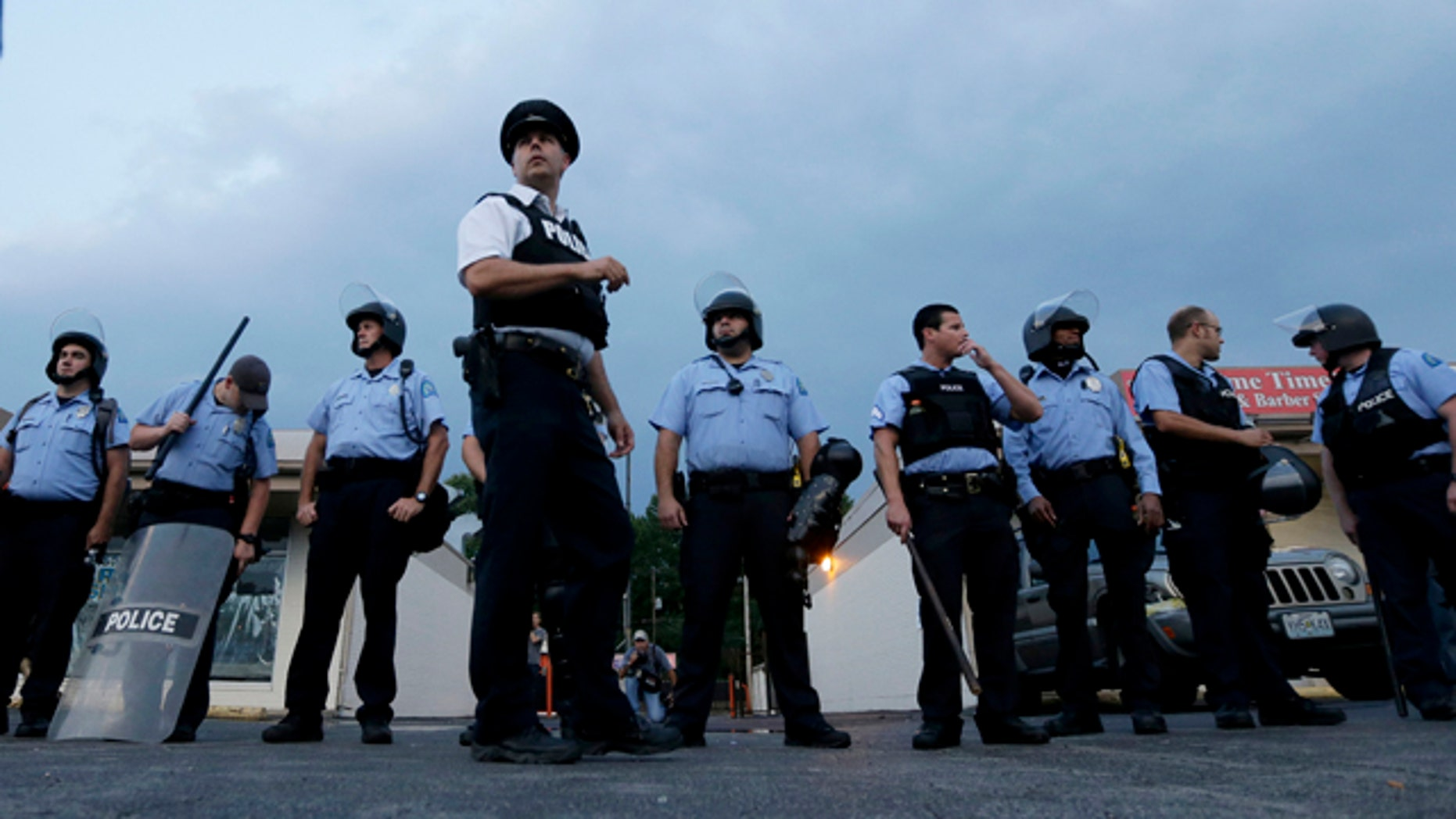 August 16, 2014: Police in riot gear prepare to take up positions as people protest the police shooting death of Michael Brown a week ago in Ferguson, Mo. (AP Photo/Charlie Riedel)
