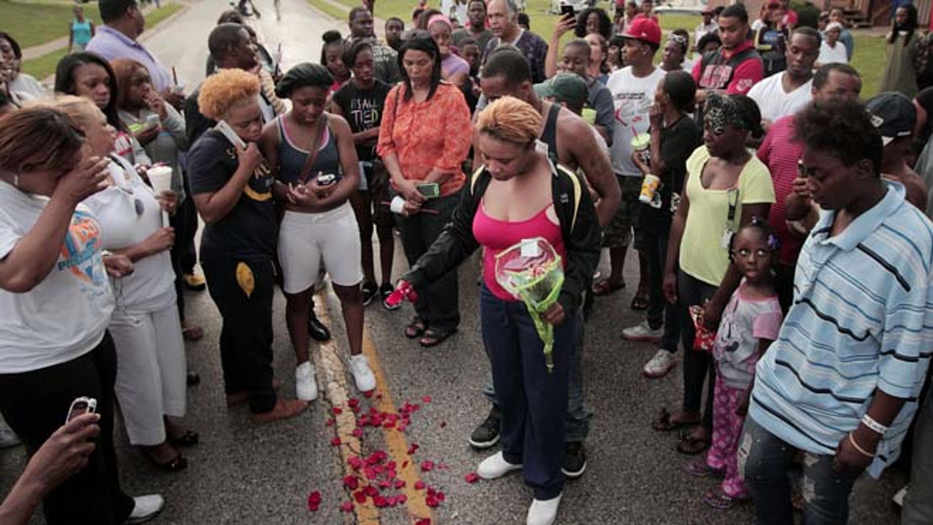 Aug. 9, 2014: Lesley McSpadden, center, drops rose petals on the blood stains from her 18-year-old son Michael Brown who was shot and killed by police in the middle of the street in Ferguson, Mo., near St. Louis. (AP/St. Louis Post-Dispatch, Huy Mach)