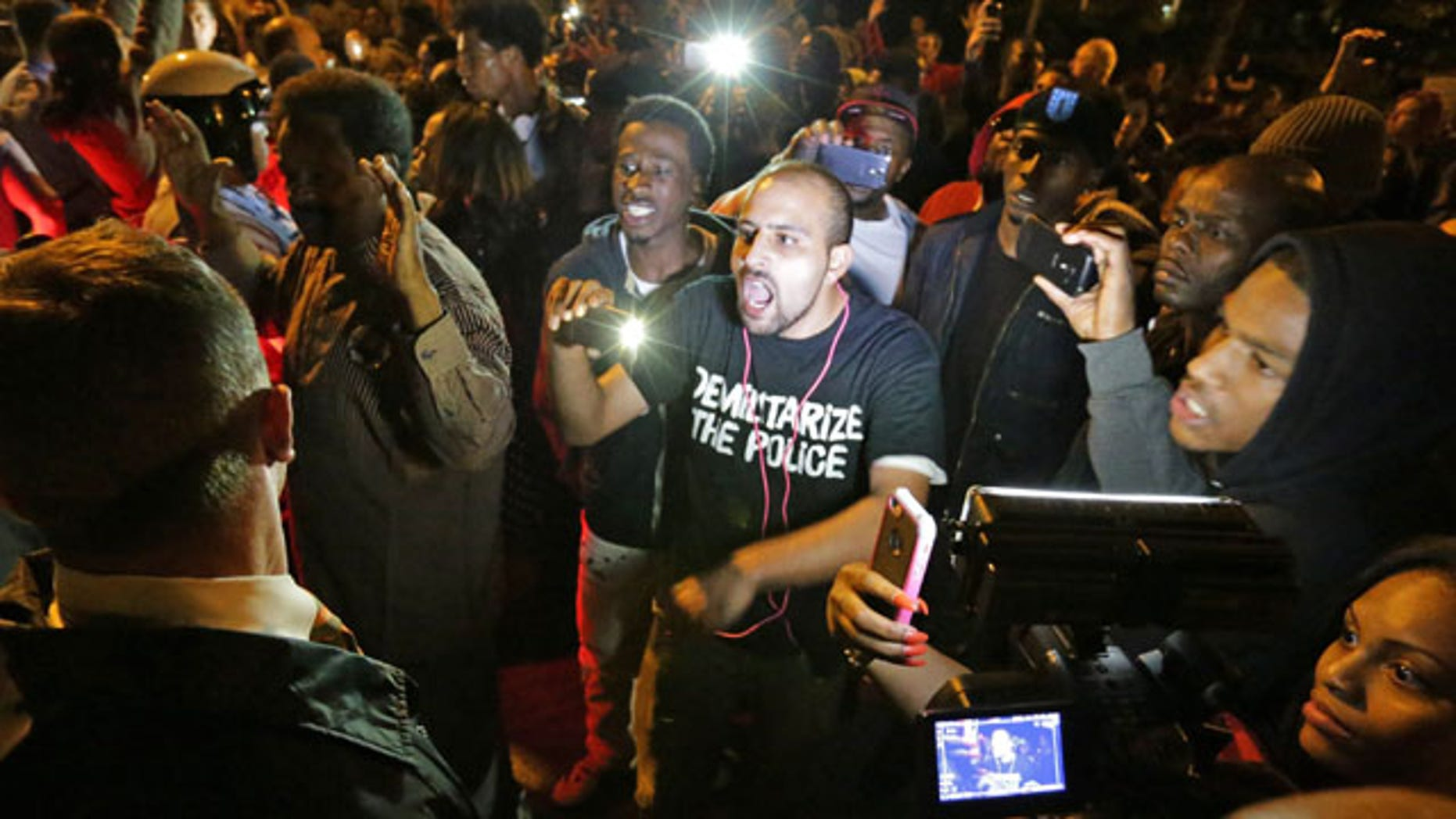 October 8, 2014: Crowds confront police near the scene in in south St. Louis where a man was fatally shot by an off-duty St. Louis police officer. St. Louis Police Lt. Col. Alfred Adkins said the 32-year-old officer was working a secondary security job late Wednesday when the shooting happened. (AP Photo/St. Louis Post-Dispatch, David Carson)
