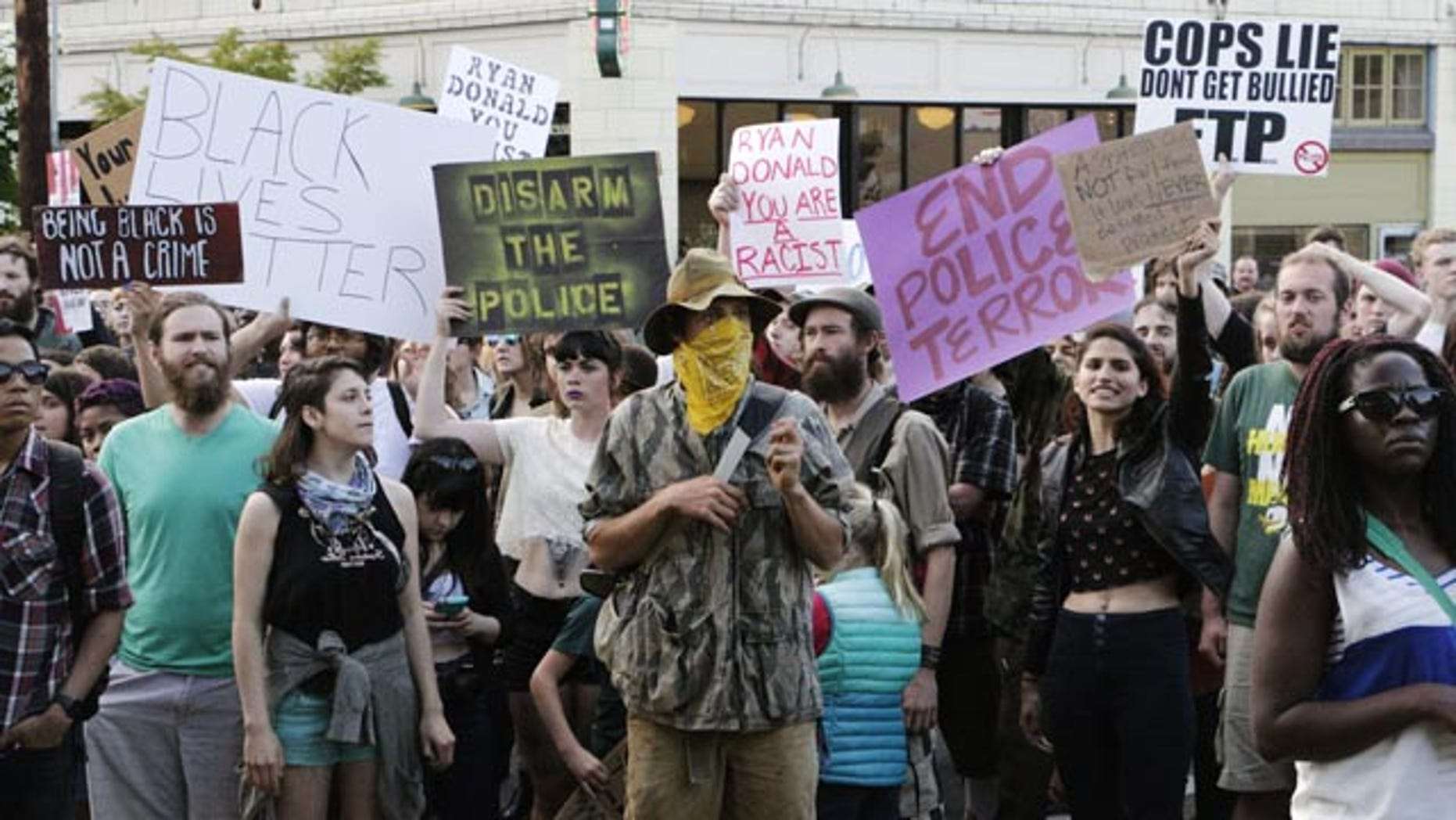 May 21, 2015: Hundreds of people protesting a police shooting gather outside of City Hall in Olympia, Wash. Police say that two stepbrothers suspected of trying to steal beer from a grocery store were unarmed when they were shot by an officer who later confronted them. (AP Photo/Rachel La Corte)