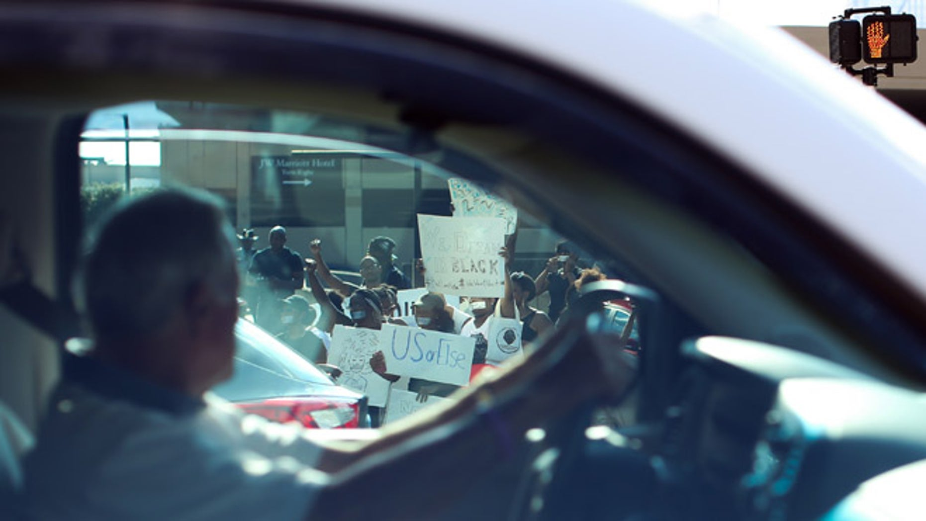 A driver passes demonstrators as they block an entrance to Lenox Square Mall during a Black Lives Matter protest in Atlanta, Saturday, Sept. 24, 2016, in response to the police shooting deaths of Terence Crutcher in Tulsa, Okla. and Keith Lamont Scott in Charlotte, N.C. The Black Lives Matter chapter of Atlanta is boycotting major retailers following the recent police shooting deaths involving black men. (AP Photo/Branden Camp)