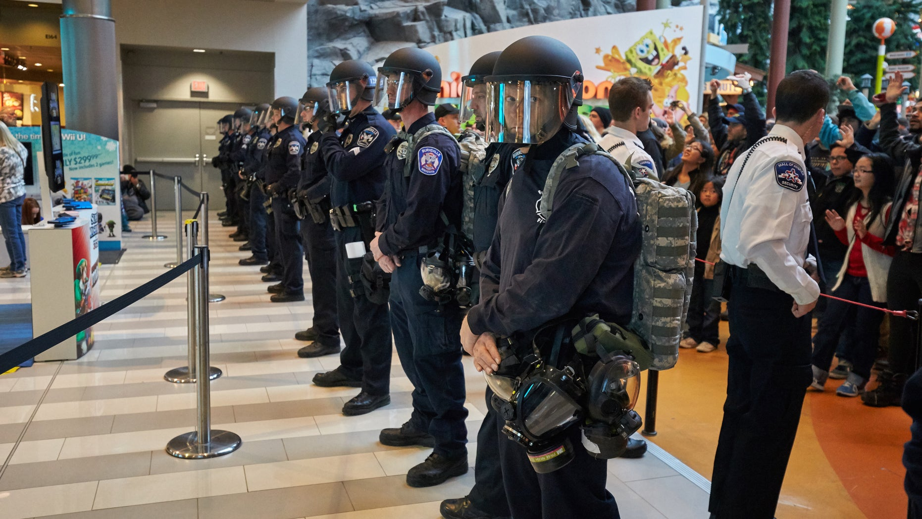 """BLOOMINGTON, MN - DECEMBER 20: Police move thousands of protesters from the group """"Black Lives Matter"""" out of the mall after they disrupted holiday shoppers on December 20, 2014 at Mall of America in Bloomington, Minnesota. (Photo by Adam Bettcher/Getty Images)"""