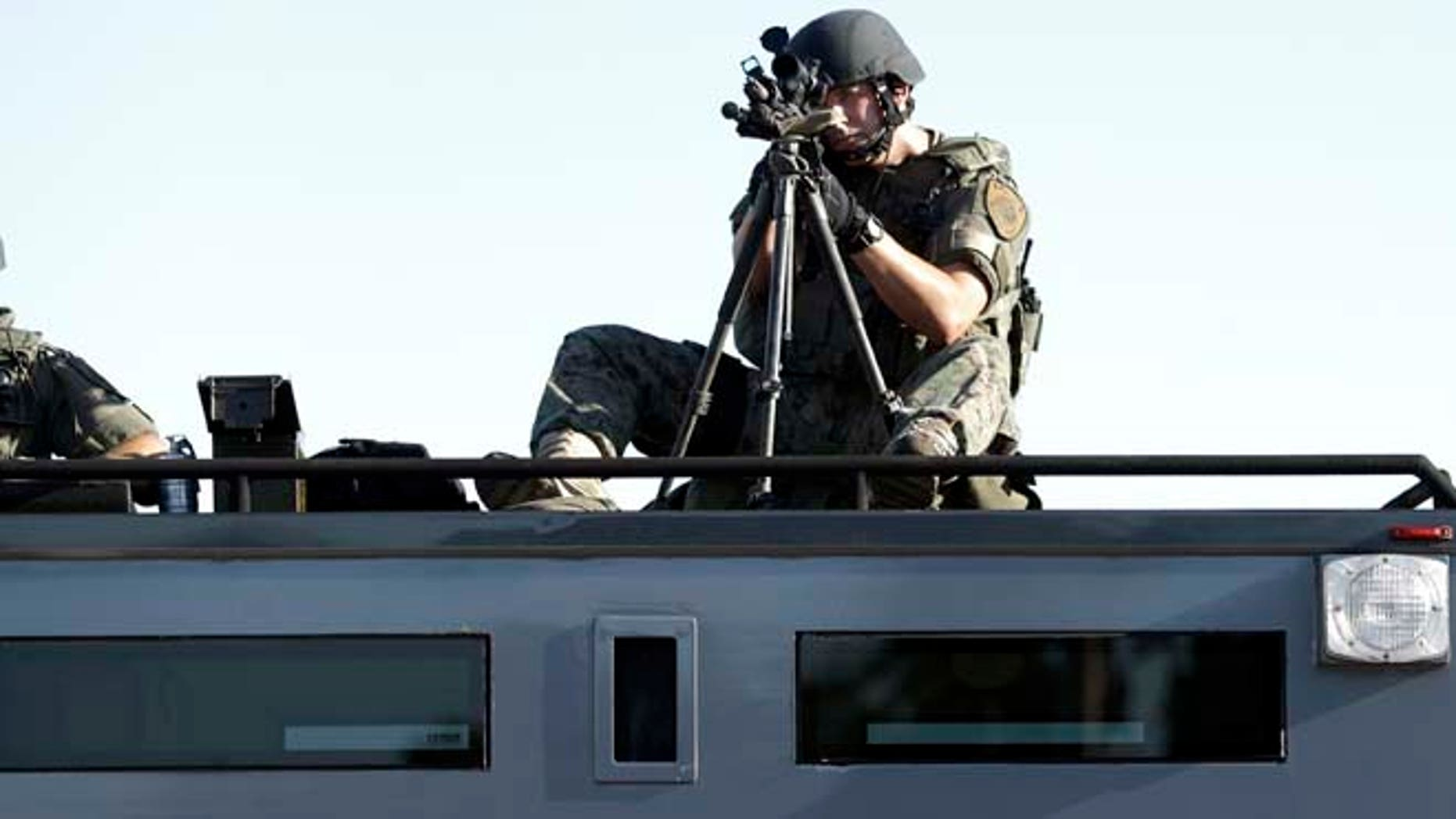 Aug. 13, 2014: A member of the St. Louis County Police Department trains his weapon on a relatively small group of protesters in Ferguson, Mo.