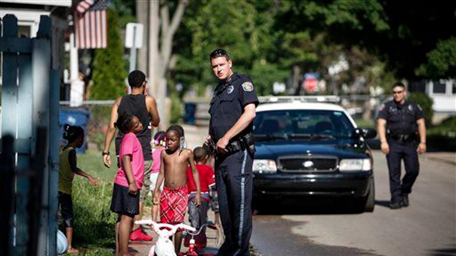 Kalamazoo Public Safety Officer Jason Gates, center, and Officer Joe Hutson, far right, stop on Hays Park Avenue in the Edison neighborhood, Friday, June 6, 2014 in Kalamazoo, Mich.