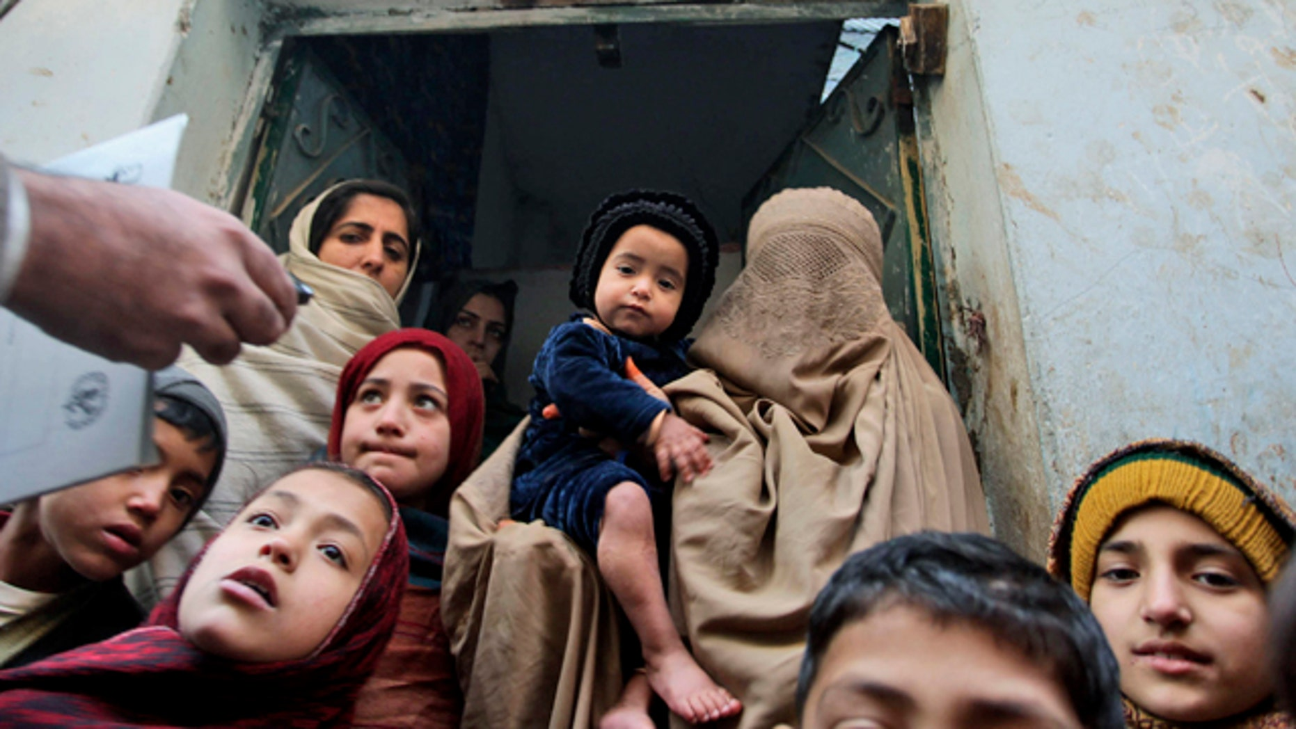 In this Dec. 28, 2010 file photo, a Pakistani health worker, left, visits families to inform them on polio in Peshawar, Pakistan. In his 2009 speech to the Muslim world, President Obama announced a new effort to eradicate polio, which persists in three Muslim countries.