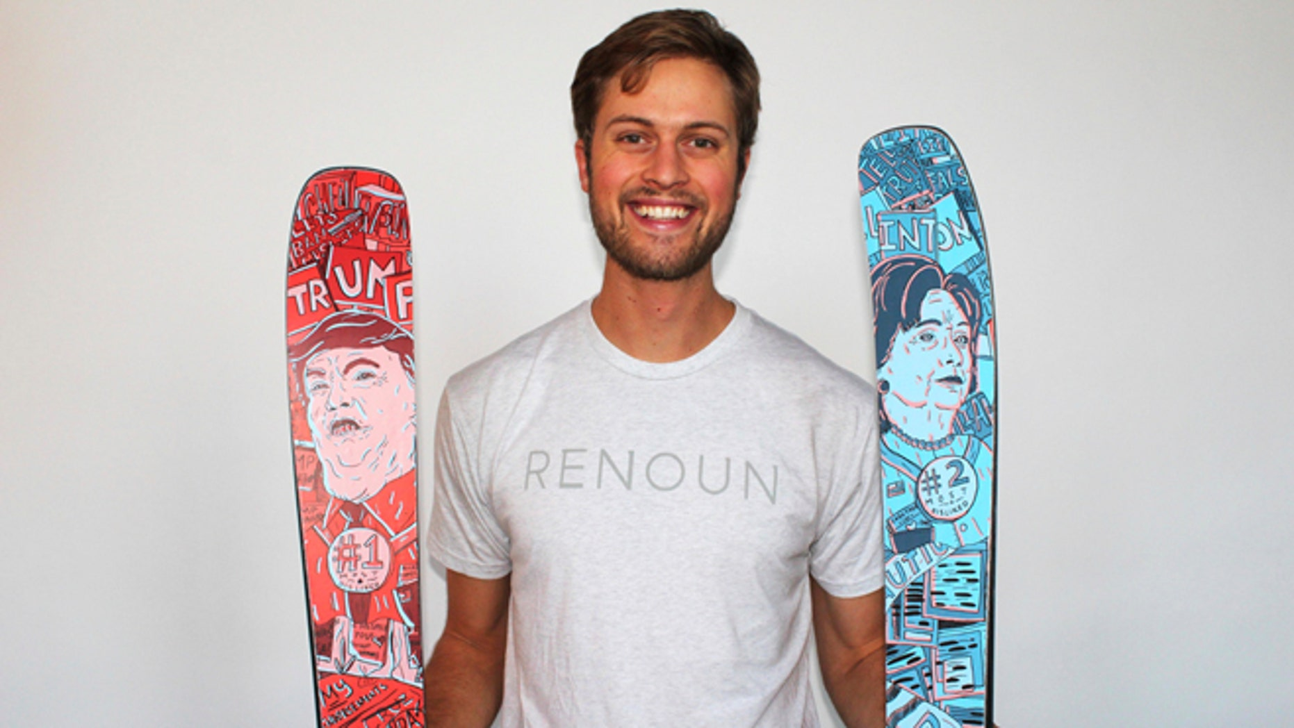 In this photo provided by Renoun, CEO Cyrus Schenck, poses with a  pair of skis featuring Hillary Clinton imagery, at right,  and Donald Trump, at left. (Courtesy of  Renoun via AP)