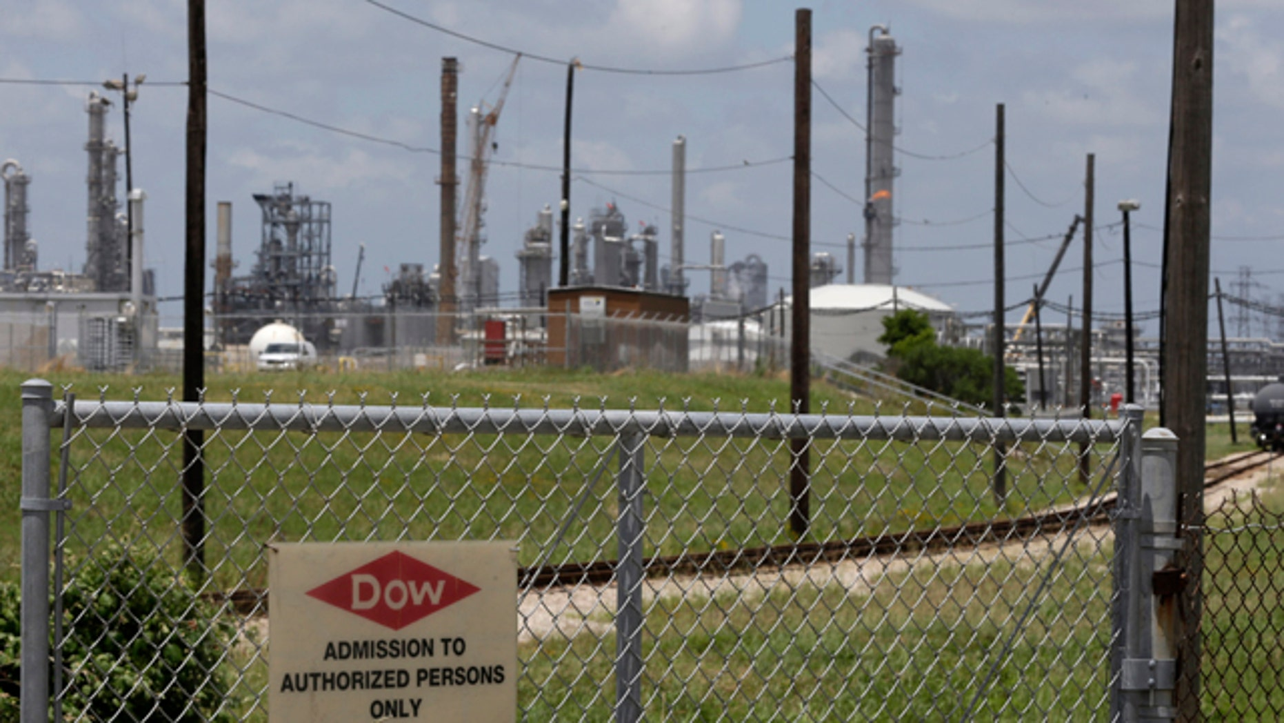 May 22, 2014: A sign is posted on a roadside fence outside a Dow Chemicals plant in Freeport, Texas. (AP Photo/Pat Sullivan)