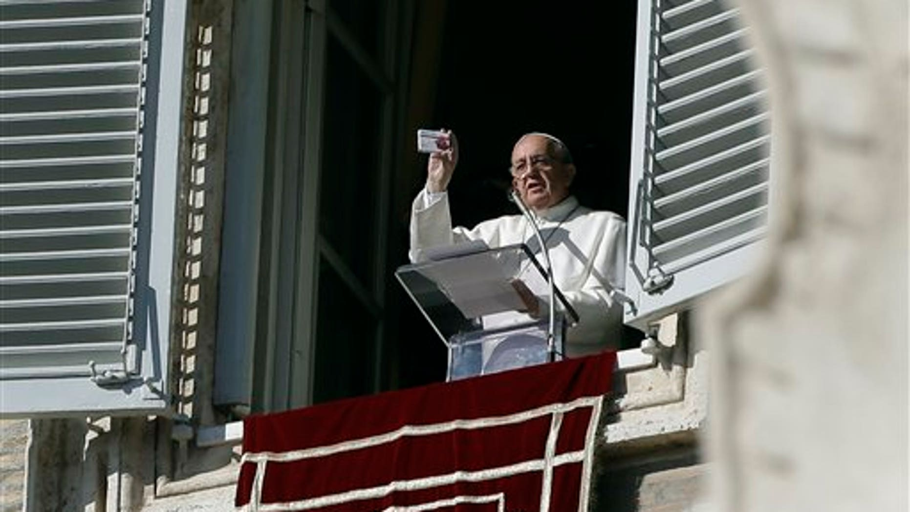 Pope Francis shows a rosary in a box designed to resemble a packets of pills, during his traditional Sunday's appearance from his studio overlooking St. Peter's Square at the Vatican, Sunday, Nov. 17, 2013. Joking that he's like a pharmacist, Pope Francis is promoting prayer as medicine for the heart. (AP Photo/Gregorio Borgia)