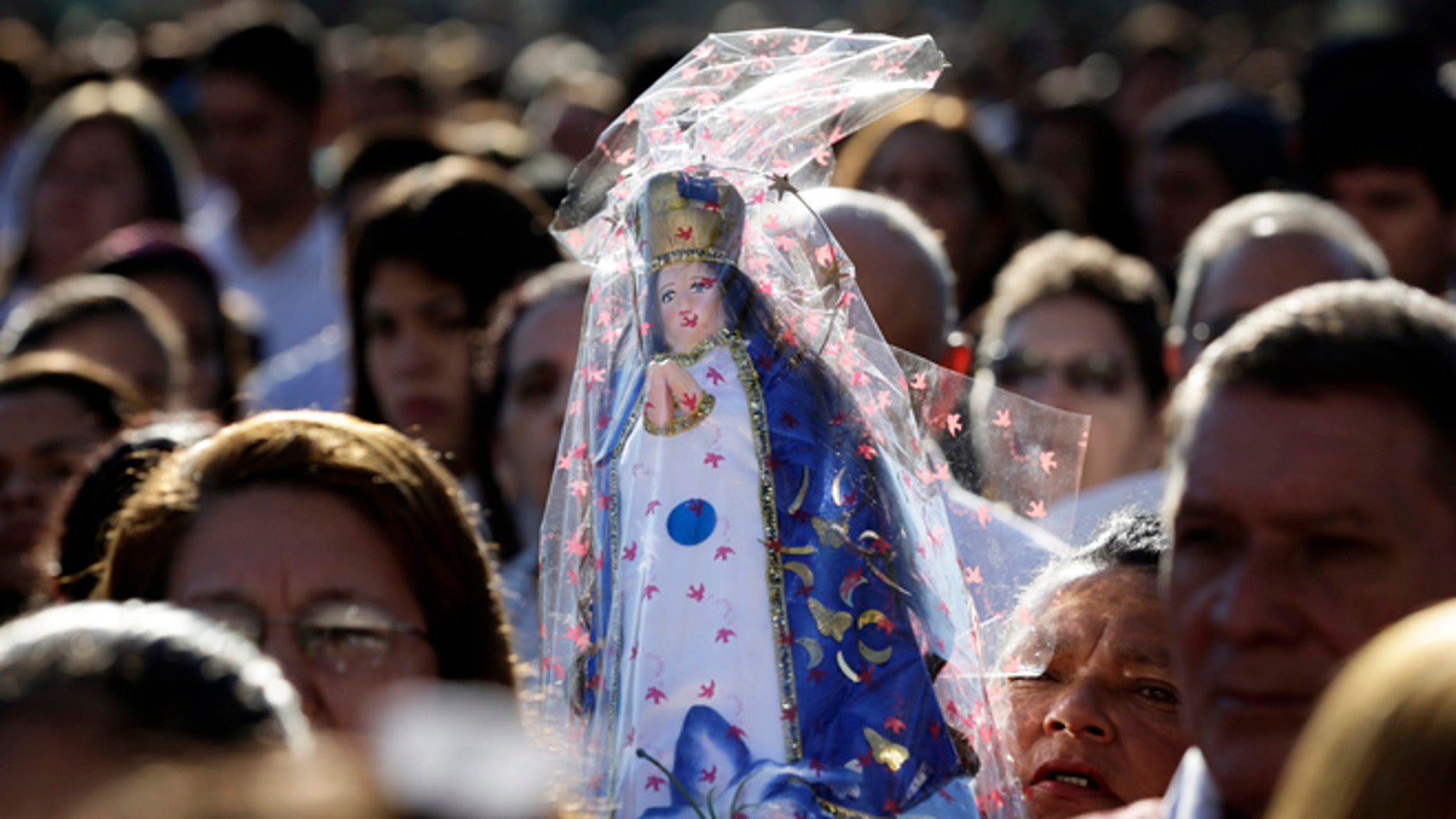 FILE - In this June 7, 2015, file photo, a woman carries a Caacupe virgin replica during Corpus Christi mass in Caacupe city, Paraguay. Hundreds of thousands turn out every December to worship before the little wooden statue of the Virgin Mary, who wears a crown over her long hair, with a billowing white robe and a blue cloak. (AP Photo/Jorge Saenz, File)