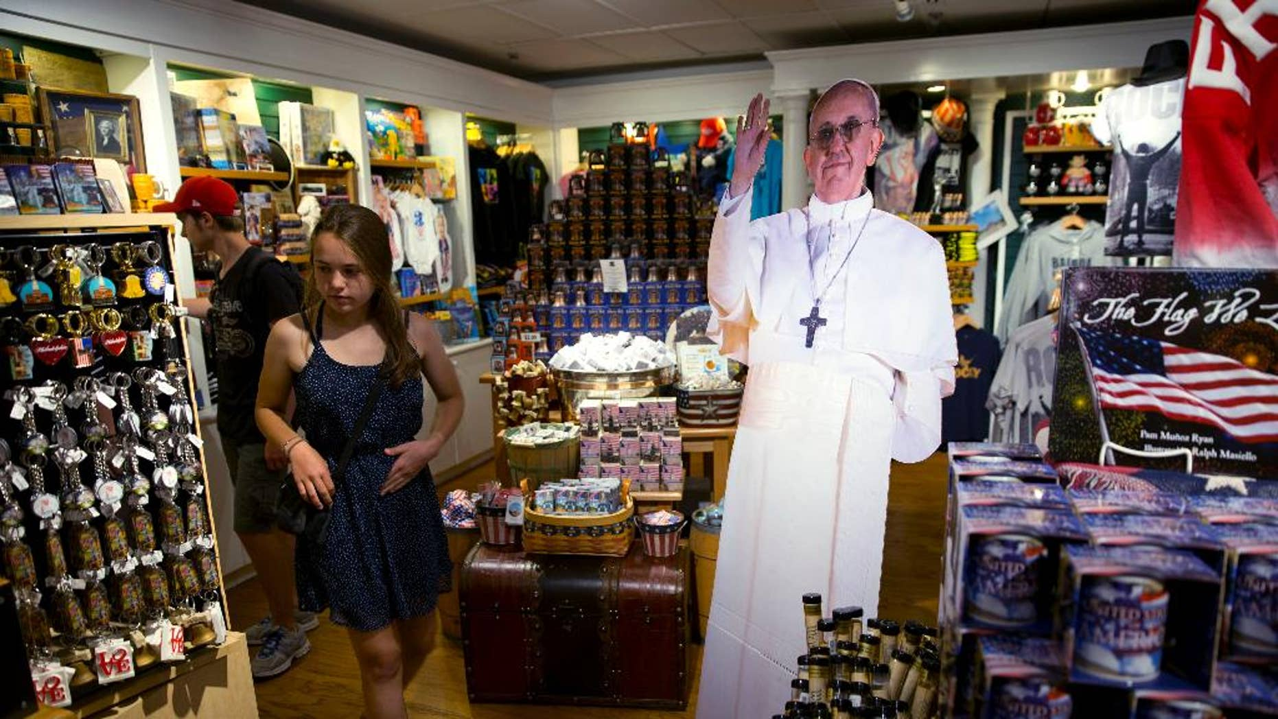 In this Monday, Aug. 10, 2015, photo, a tourist passes cutout of Pope Francis at Making History, a Philadelphia themed gift shop Philadelphia. The cutouts have been popping up in areas around the region weeks ahead of pope's scheduled visit. (AP Photo/Matt Rourke)