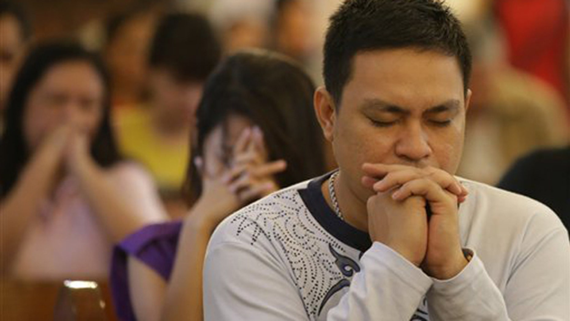 "CORRECTS MONTH- Filipino Catholics pray during a mass at the Our Lady of Remedies Parish Church in Manila, Philippines Sunday, Sept. 22, 2013. Catholics around the globe are expressing mixed but mostly positive reactions to Pope Francis' recent remarks that the church has become too focused on ""small minded rules"" on hot-button issues like homosexuality and abortion. (AP Photo/Aaron Favila)"
