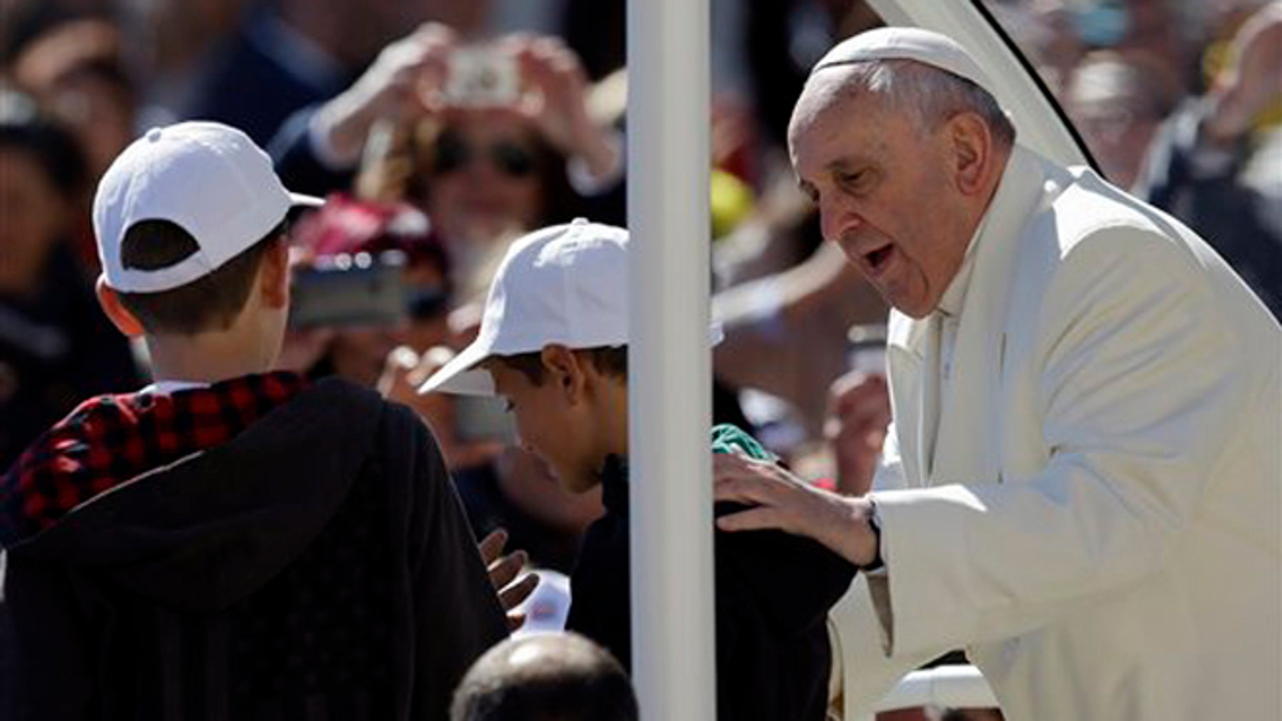 Pope Francis greets 11-year-olds Livio Bastianelli and Davide Maria Bianchi Wednesday, April 16, 2014.