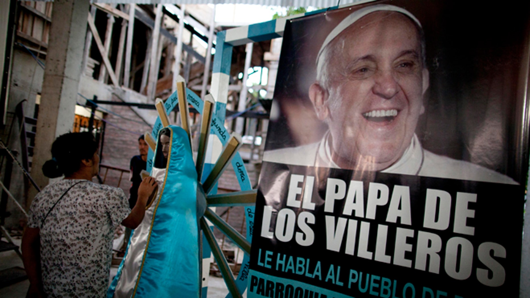 """A woman touches a religious figure beside a banner of Pope Francis reading in Spanish, """"The Pope of the people of the slum"""" as she attends a mass in his honor at the 1-11-14 slum's church in Buenos Aires, Argentina, Thursday, March 13, 2014. On the day of the first anniversary of the Pope's election, people from the 1-11-14 slum gather at their church to watch an interview that Pope Francis gave recently from his residence at the Vatican to FM Bajo Flores, a community radio station that broadcasts from the slum. (AP Photo/Natacha Pisarenko)"""