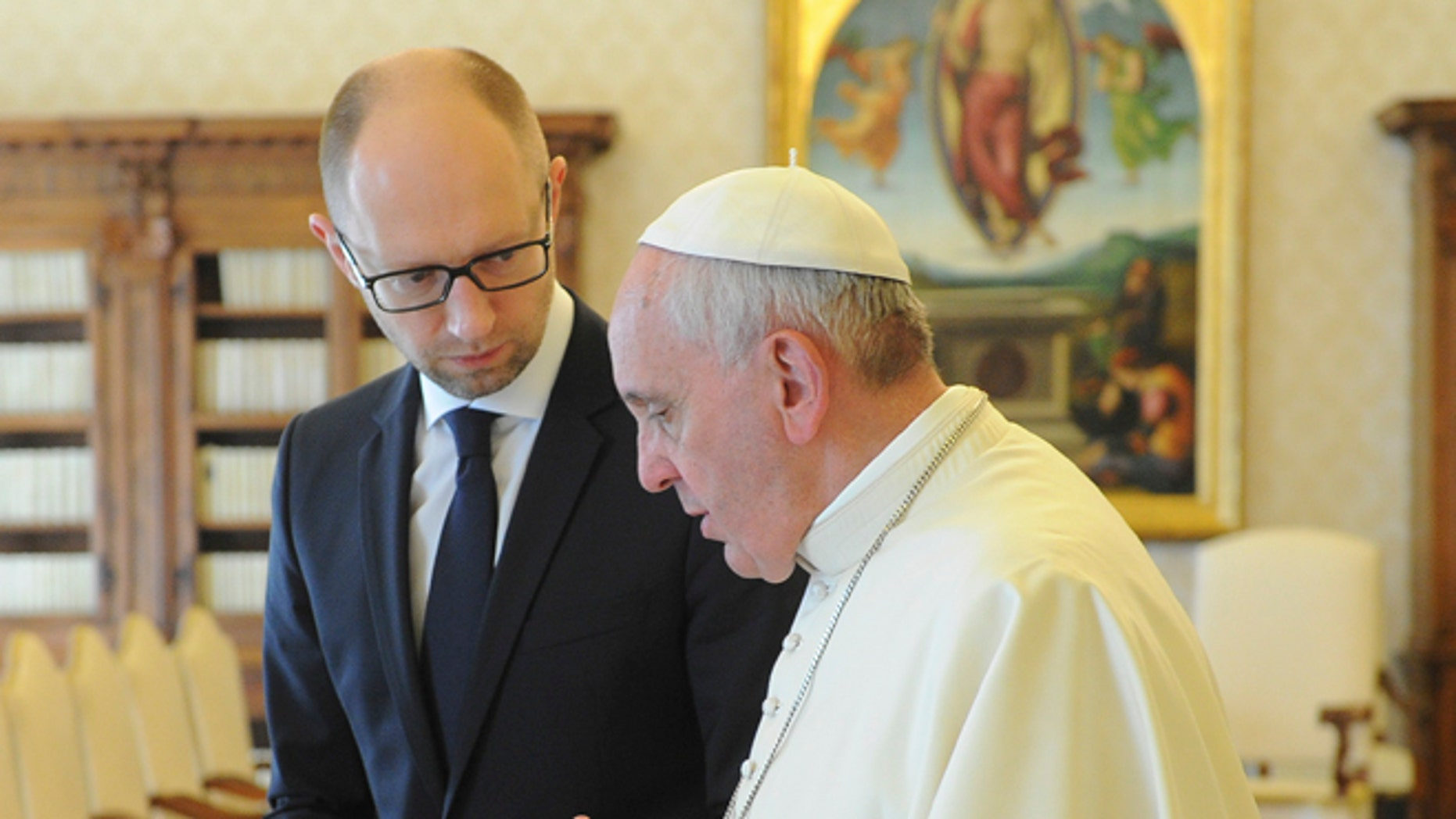 Ukrainian Prime Minister Arseny Yatsenyuk, left, listens to Pope Francis on the occasion of their private audience at the Vatican, Saturday, April 26, 2014. Yatsenyuk is in Rome to attend Sunday's canonization ceremony for John Paul II and John XXIII where Pope Francis will elevate the two popes to sainthood. (AP Photo/Andrew Kravchenko, Pool)