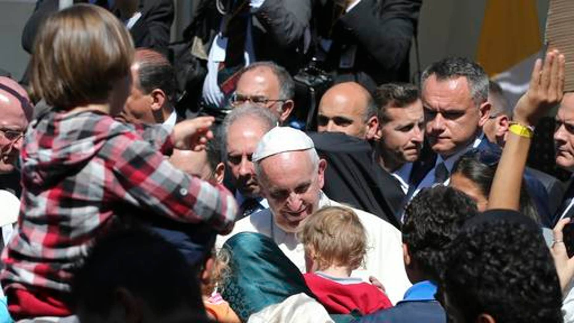 FILE - In this April 16, 2016 file photo, Pope Francis meets migrants at the Moria refugee camp on the Greek island of Lesbos. The pope, in his annual message for the World Day of Migrants and Refugees on Thursday, Oct. 13, 2016, denounced the forced repatriation of unaccompanied children migrants who flee wars and poverty, saying countries should try to meet their needs rather than return them to uncertain futures back home. (AP Photo/Petros Giannakouris, File)