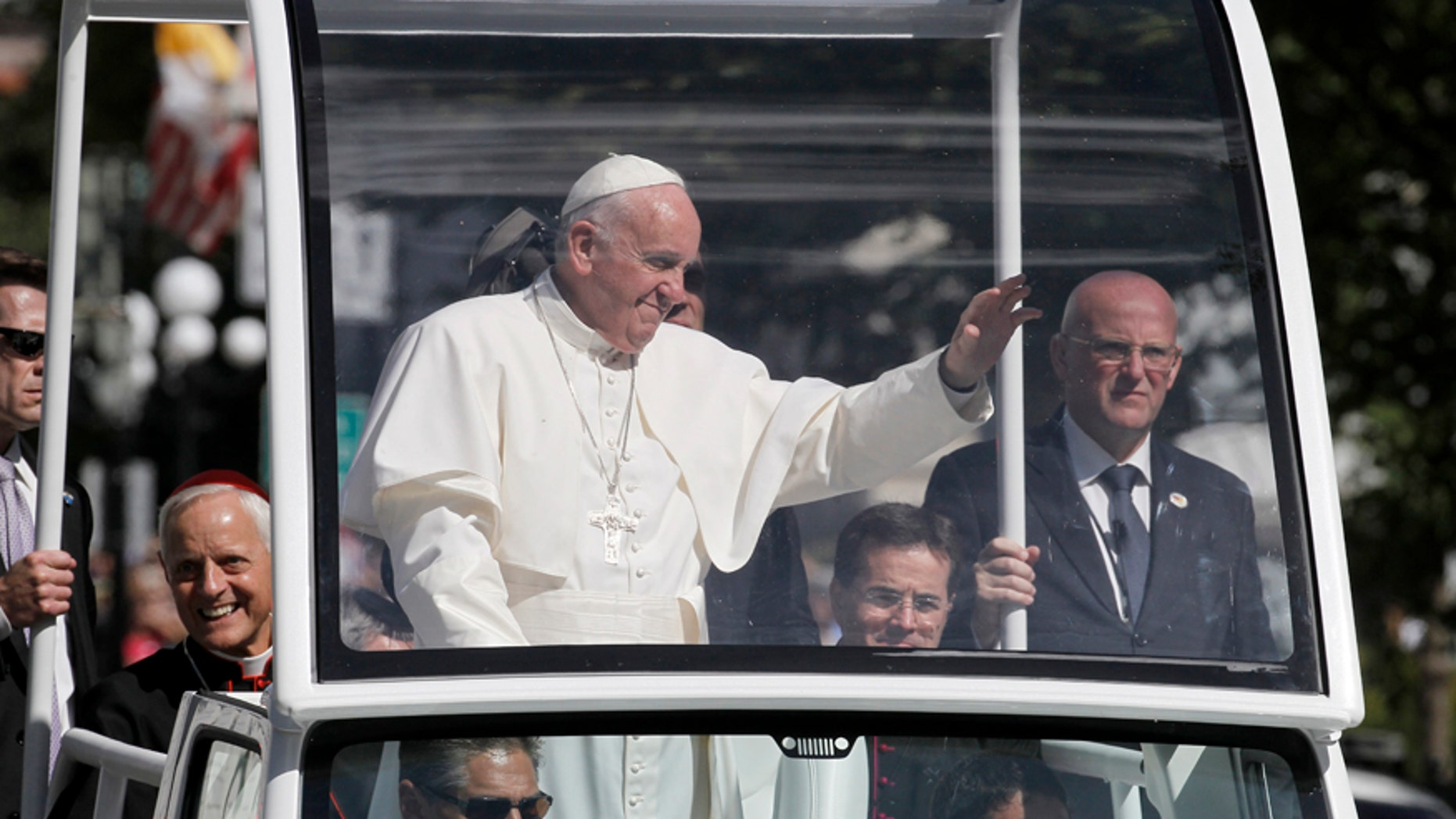 Pope Francis waves to the crowd from the popemobile during a parade in Washington, Wednesday, Sept. 23, 2015.