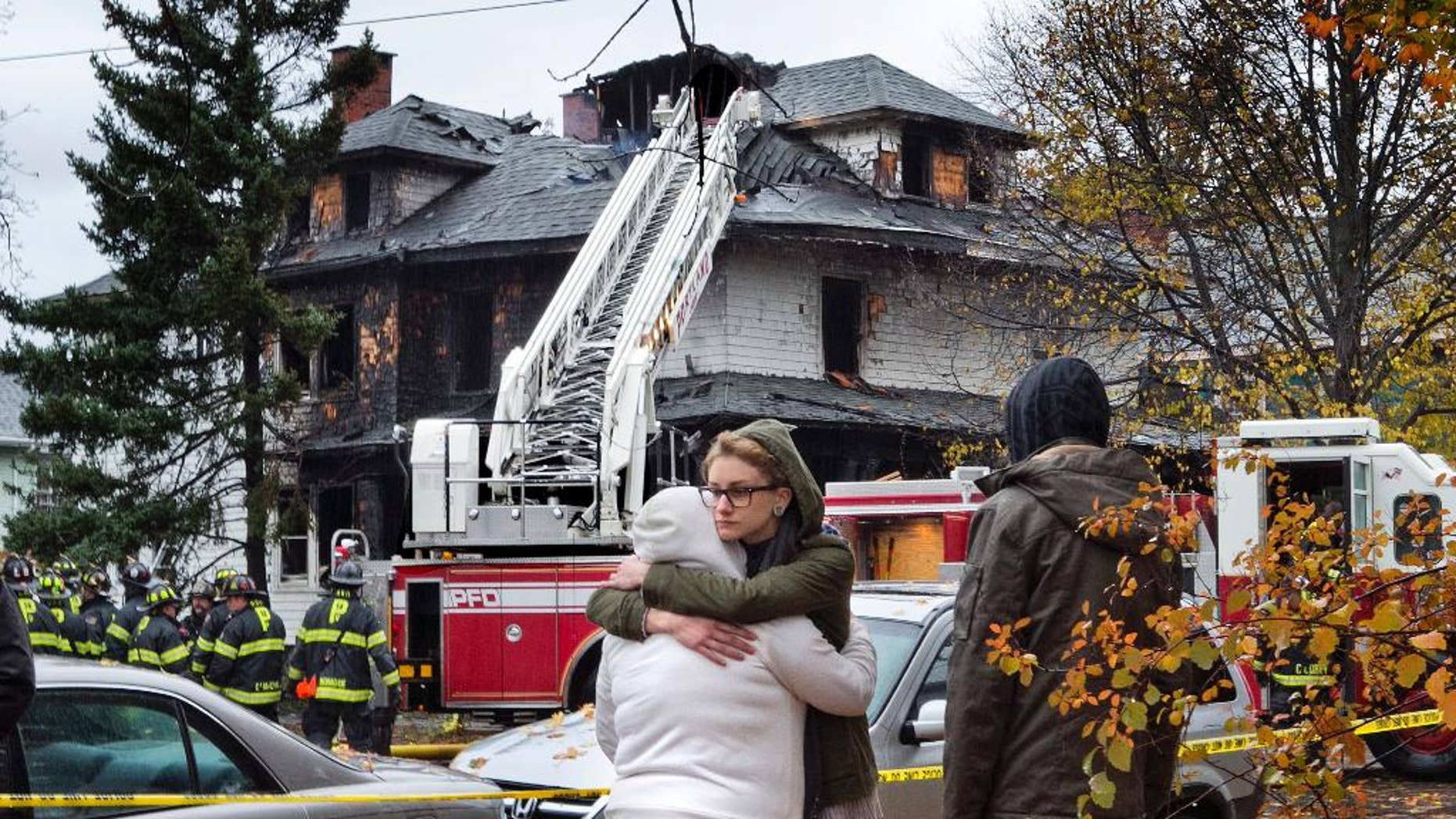 FILE - In this Nov. 1, 2014, file photo, friends of a victim of a fatal apartment building fire console one another other in Portland, Maine. The owner of an apartment house where six people died in a fire that started hours after a Halloween party has been indicted on six counts of manslaughter, authorities announced on Friday, July 10, 2015. (AP Photo/Robert F. Bukaty, File)