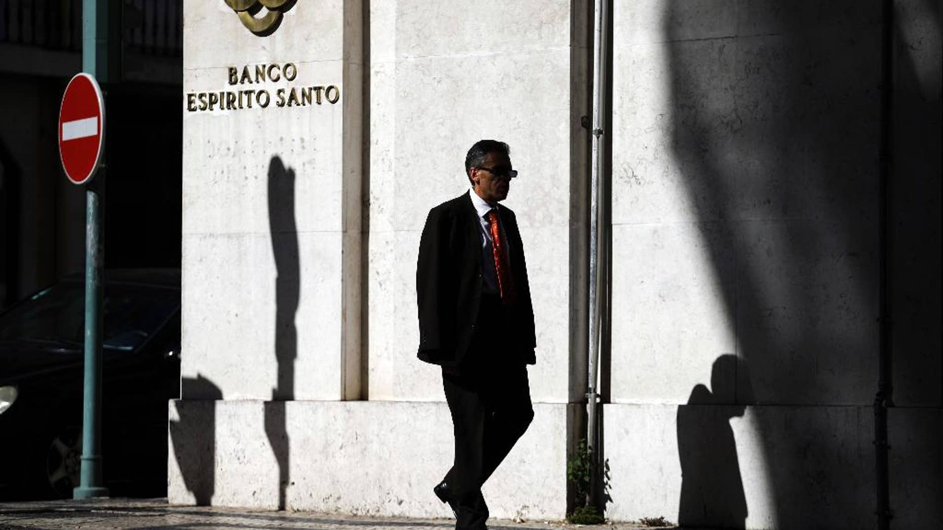 A man walks past a Portuguese bank Banco Espirito Santo's building in downtown Lisbon, Friday July 11, 2014. Senior Portuguese officials gave assurances Friday about the soundness of Portugal's biggest bank, seeking to defuse tension after world markets went into a spin over fears that Banco Espirito Santo's troubles could reignite Europe's financial difficulties. (AP Photo/Francisco Seco)