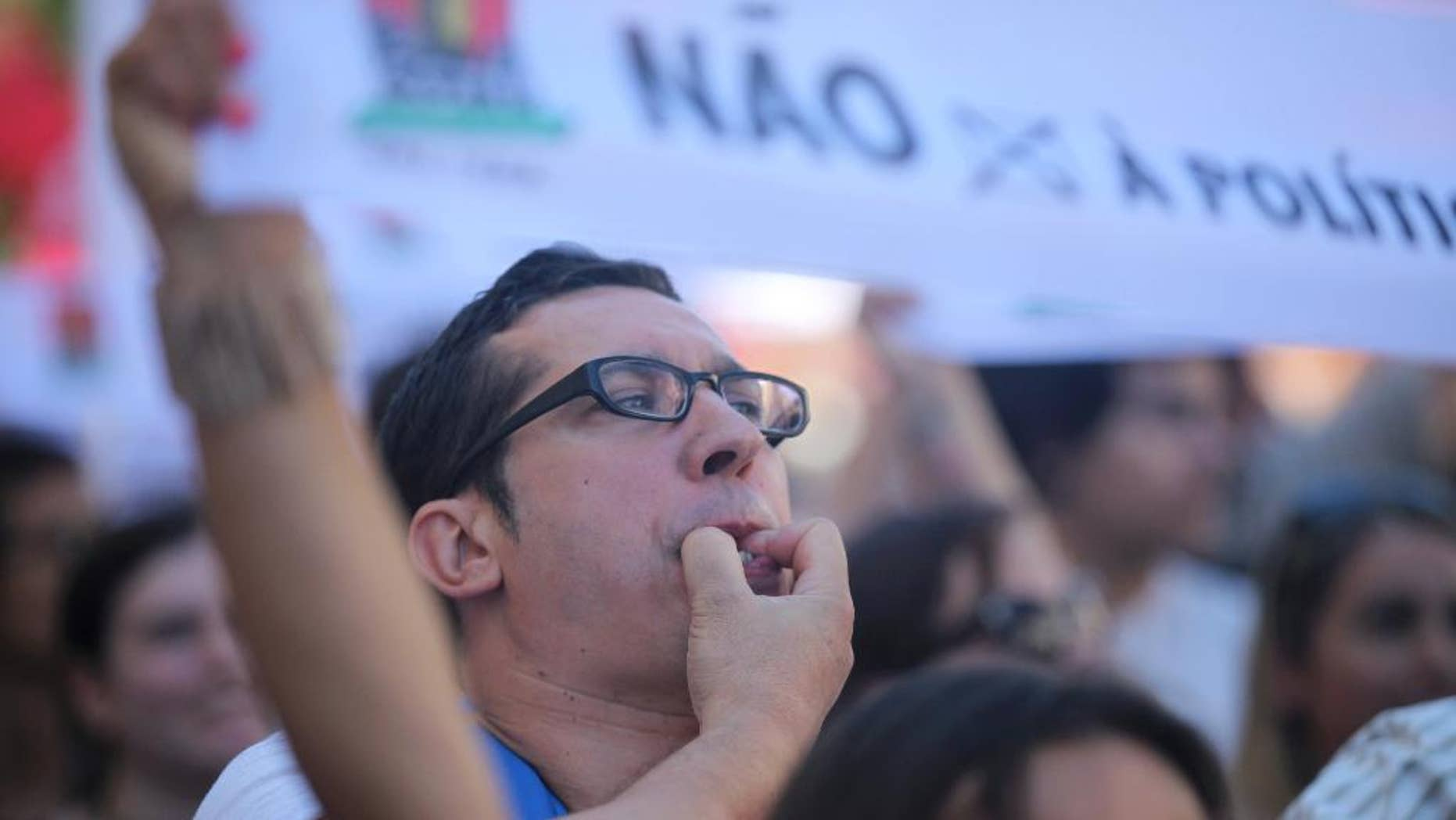 "A man whistles during a workers' unions demonstration against the government's austerity measures outside the parliament in Lisbon, Wednesday, July 22 2015. On Tuesday the Portuguese president began hearing political leaders to decide on a date for the country's next general elections to be held after the summer. The banner reads ""No to right wing policy"". (AP Photo/Armando Franca)"