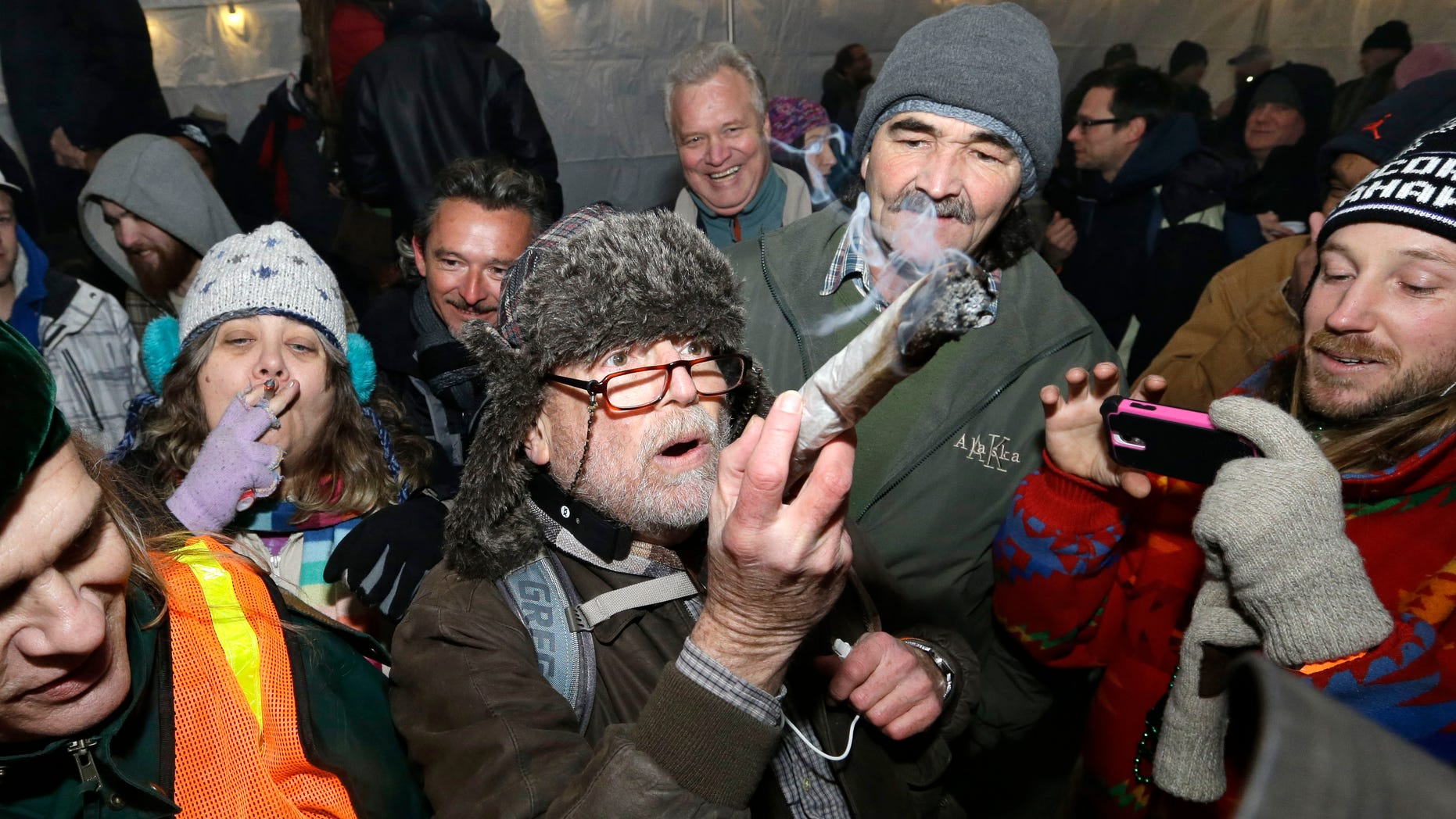 Dec. 6, 2013: A partier looks over a marijuana joint, made from a full ounce of pot, before taking a hit on it at a pot party at the Seattle Center, in Seattle.