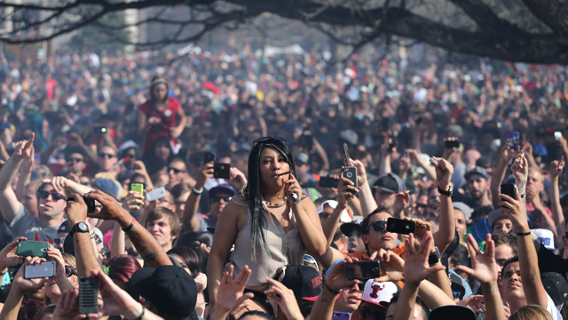 April 20, 2014: Partygoers listen to live music on the second of two days at the annual 4/20 marijuana festival in Denver. The annual event is the first 420 marijuana celebration since retail marijuana stores began selling in January 2014. (AP Photo/Brennan Linsley)