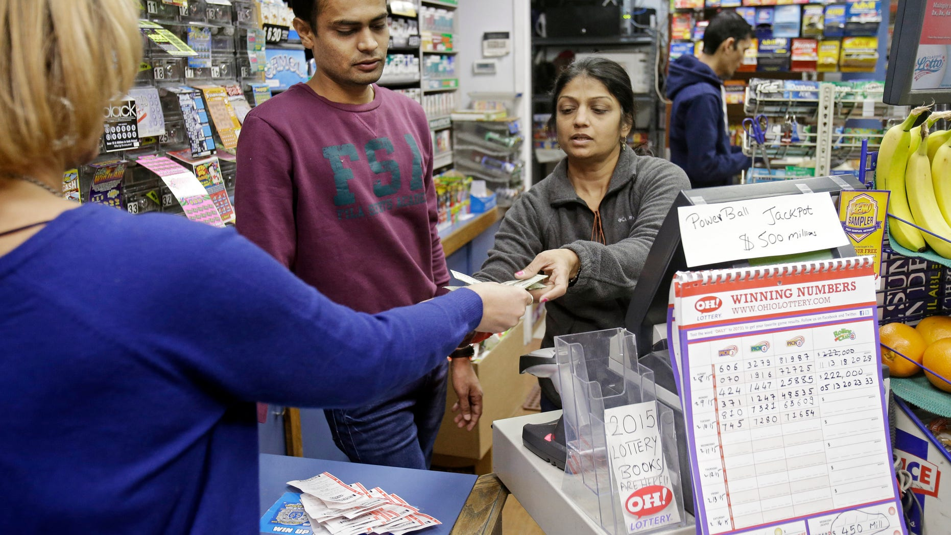 Swati Patel, hands Powerball tickets to a customer as Manish Desai watches at Gateway Newstands in Cleveland Wednesday, Feb. 11, 2015. The Powerball jackpot has climbed to $500 million, making Wednesday night's drawing the fifth largest prize in U.S. history. (AP Photo/Mark Duncan)
