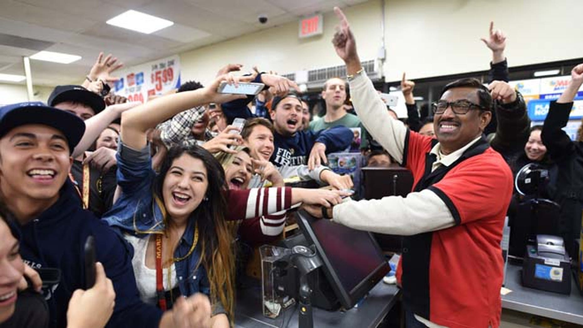 7-Eleven store clerk M. Faroqui celebrates with customers after learning the store sold a winning Powerball ticket on Wednesday, Jan. 13, 2016 in Chino Hills, Calif.  One winning ticket was sold at the store located in suburban Los Angeles said Alex Traverso, a spokesman for California lottery. The identity of the winner is not yet known. (Will Lester/The Sun via AP) MANDATORY CREDIT