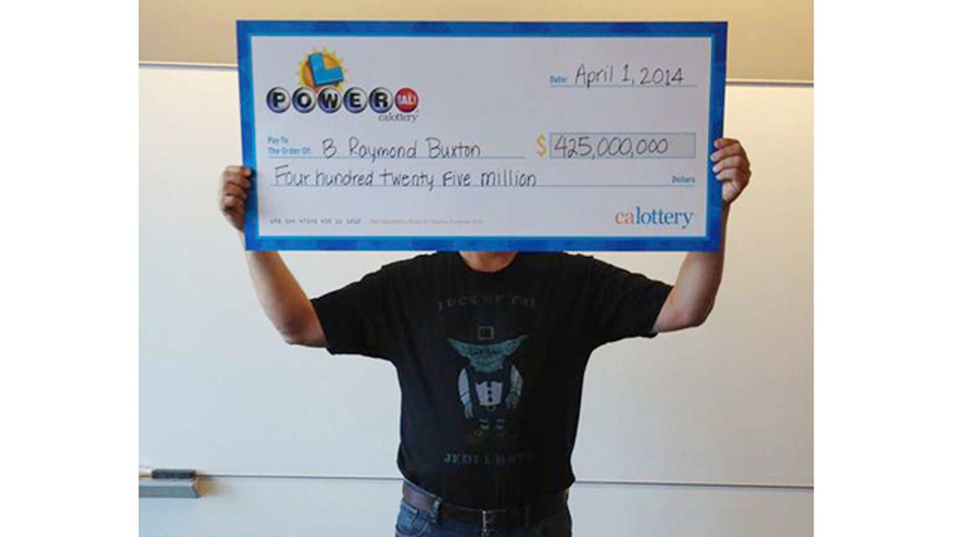April 1, 2014: This photo provided by the California Lottery shows Powerball winner B. Raymond Buxton holding a check for $425 million, in Sacramento, Calif. Buxton was wearing a shirt that featured a picture of Yoda and read, 'Luck of the Jedi I have', according to lottery officials. (AP Photo/California Lottery)