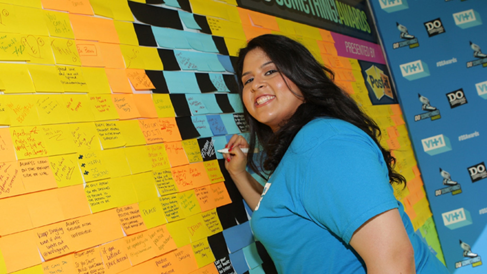 HOLLYWOOD, CA - JULY 31: Lorella Praeli of United We Dream writes messages of positivity on the Post-it Brand Wall in support of DoSomething.org at VH1's 2013 Do Something Awards at Avalon on July 31, 2013 in Hollywood, California.  (Photo by Mike Windle/Getty Images for VH1)