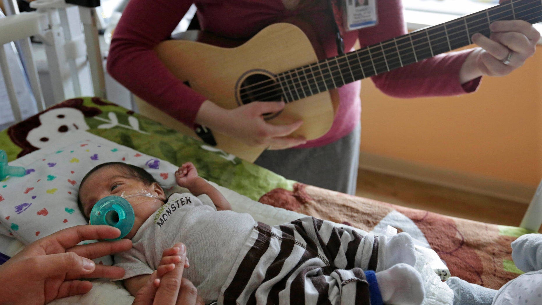 Music therapist Elizabeth Klinger, right, quietly plays guitar and sings for Augustin as he grips the hand of his mother, Lucy Morales, in the newborn intensive care unit at Ann & Robert H. Lurie Children's Hospital in Chicago.