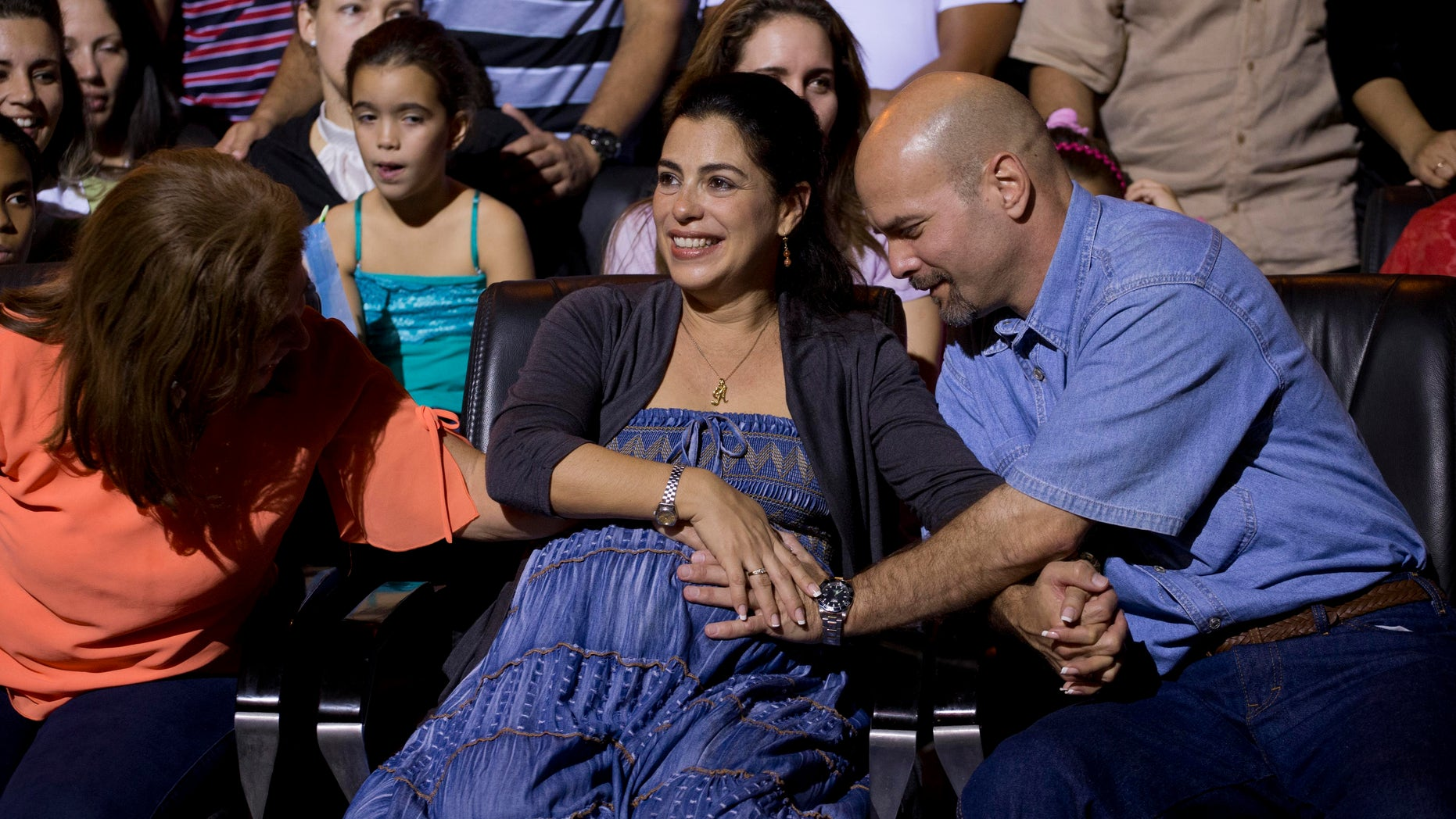 """Gerardo Hernandez, right, member of """"The Cuban Five,""""  touches the belly of his pregnant wife Adriana Perez, during a concert of singer Silvio Rodriguez in Havana, Cuba, Saturday, Dec. 20, 2014. Hernandez flew back to their homeland on Wednesday in a quiet exchange of imprisoned spies, part of a historic agreement to restore relations between the two long-hostile countries. (AP Photo/Ramon Espinosa)"""
