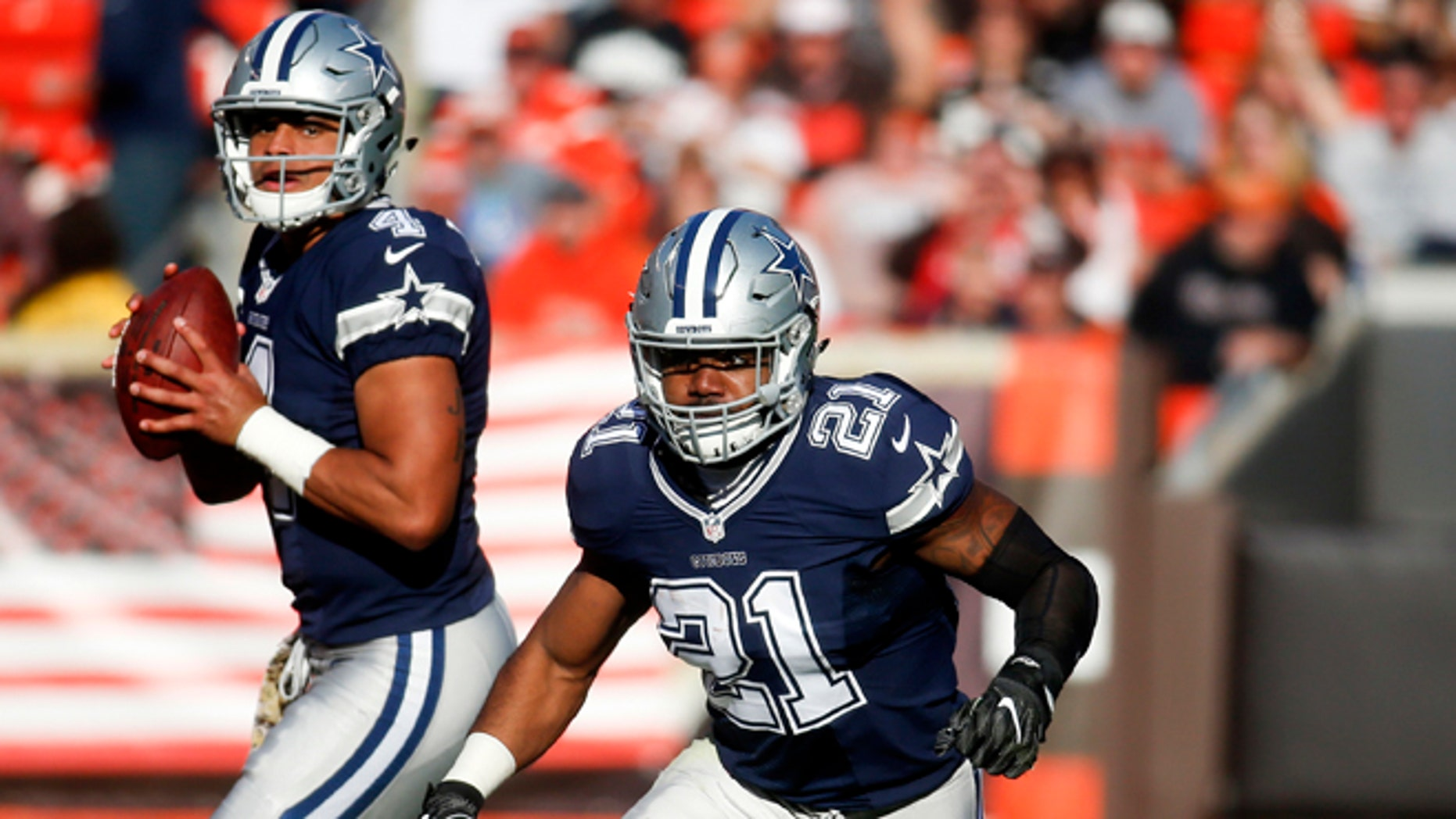 Dallas Cowboys running back Ezekiel Elliott (21) runs on a play as quarterback Dak Prescott (4) looks to pass in the second half of an NFL football game against the Cleveland Browns, Sunday, Nov. 6, 2016, in Cleveland. (AP Photo/Ron Schwane)