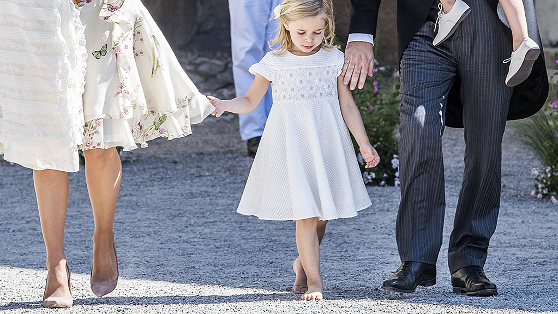 A barefoot Princess Leonore walks along side of her parents at the traditional christening ceremony for her sister, Princess Adrienne.