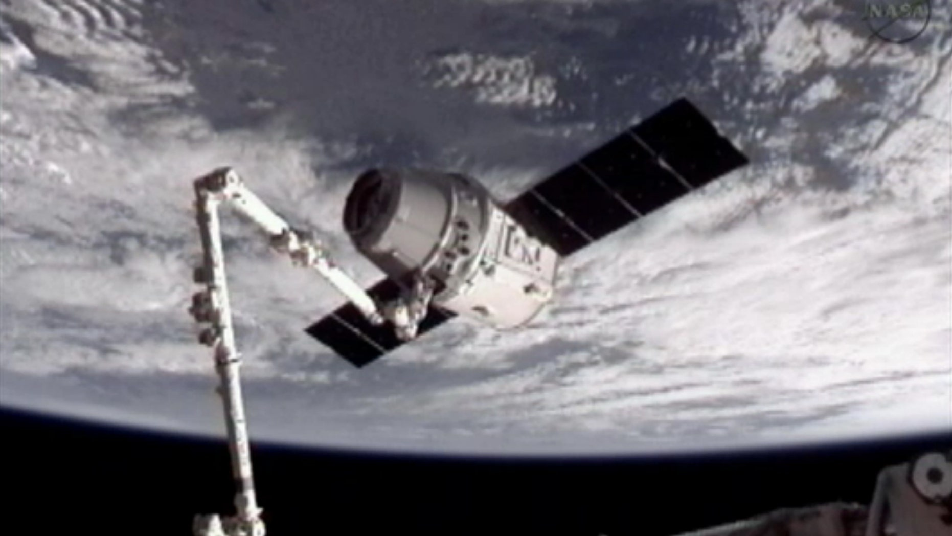 May 25, 2012: This image provided by NASA-TV shows the SpaceX Dragon commercial cargo craft, top, after Dragon was grappled by the Canadarm2 robotic arm and connected to the International Space Station.