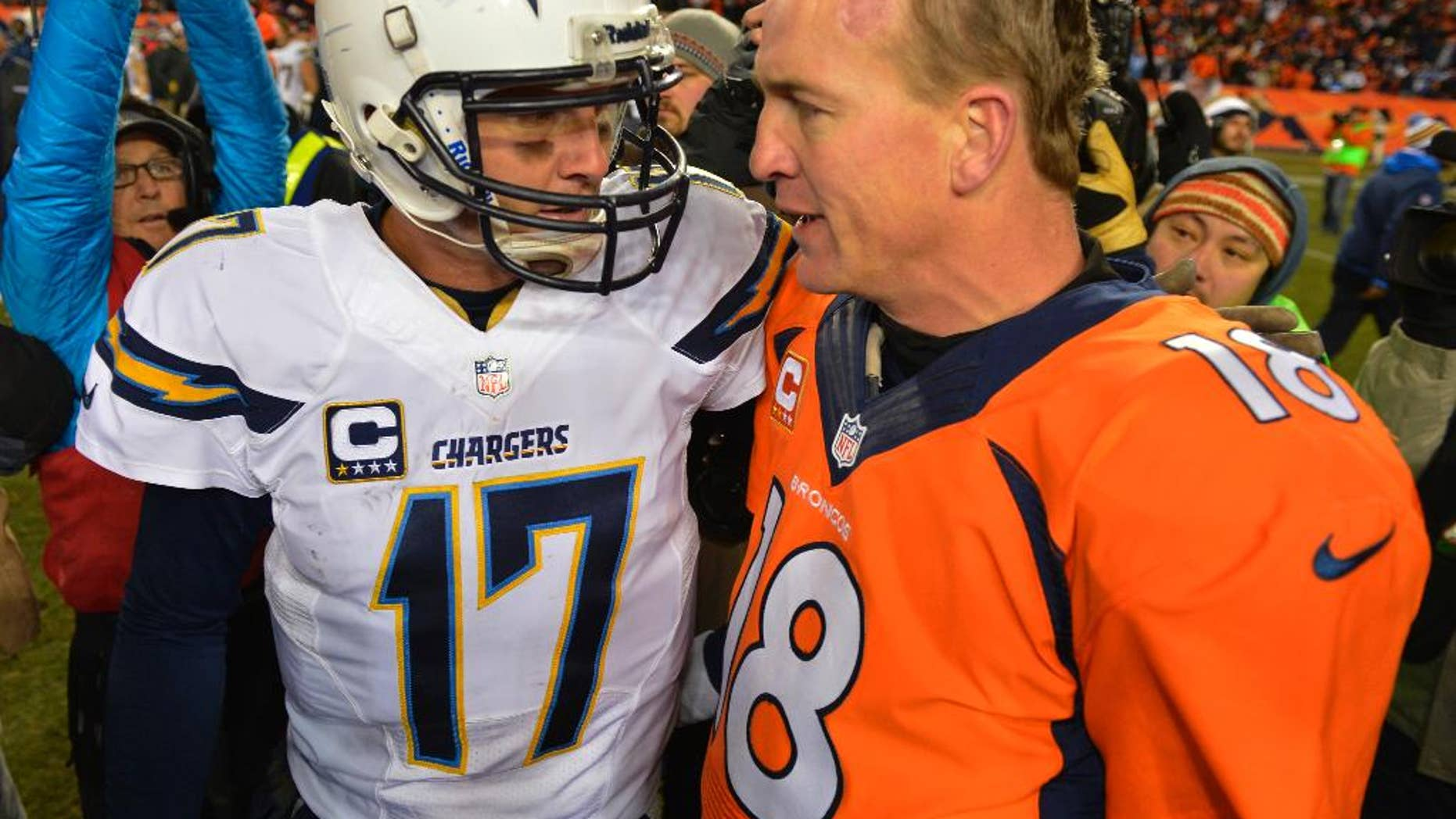 FILE - In this Jan. 12, 2014, file photo, San Diego Chargers quarterback Philip Rivers, left, and Denver Broncos quarterback Peyton Manning greet each other at midfield after the Broncos beat the Chargers 24-17 in an NFL AFC division playoff football game in Denver. The Broncos fear no one in the AFC, nor should they given their recent record. There is one opponent that gets Peyton Manning and company a bit unsettled, though, and that's who they take on Thursday night, Oct. 23, 2014, when the San Diego Chargers come visiting. (AP Photo/Jack Dempsey, File)