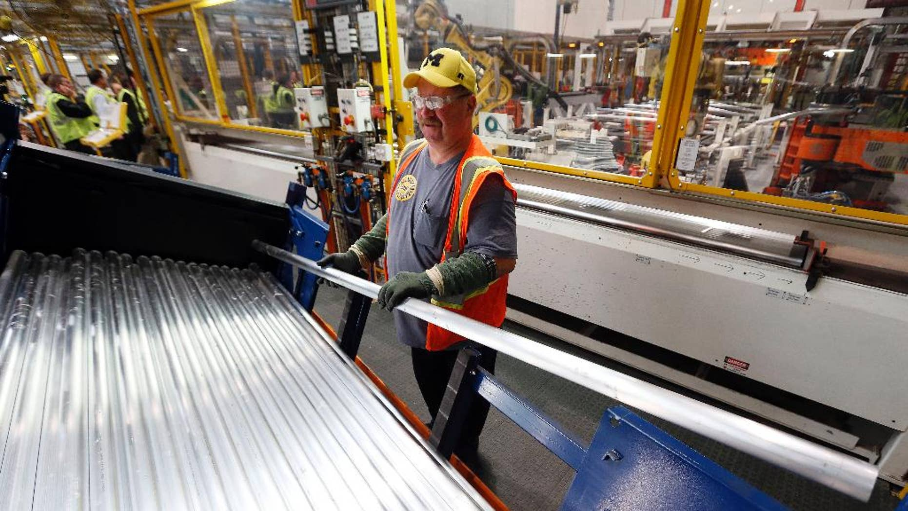 In this Nov. 11, 2014 photo, Tom Peters moves material for roof rails on the production line for the 2015 Ford F-150 at the Dearborn Truck Plant in Dearborn, Mich. The Labor Department releases the Producer Price Index for October on Tuesday, Nov. 18, 2014. (AP Photo/Paul Sancya)