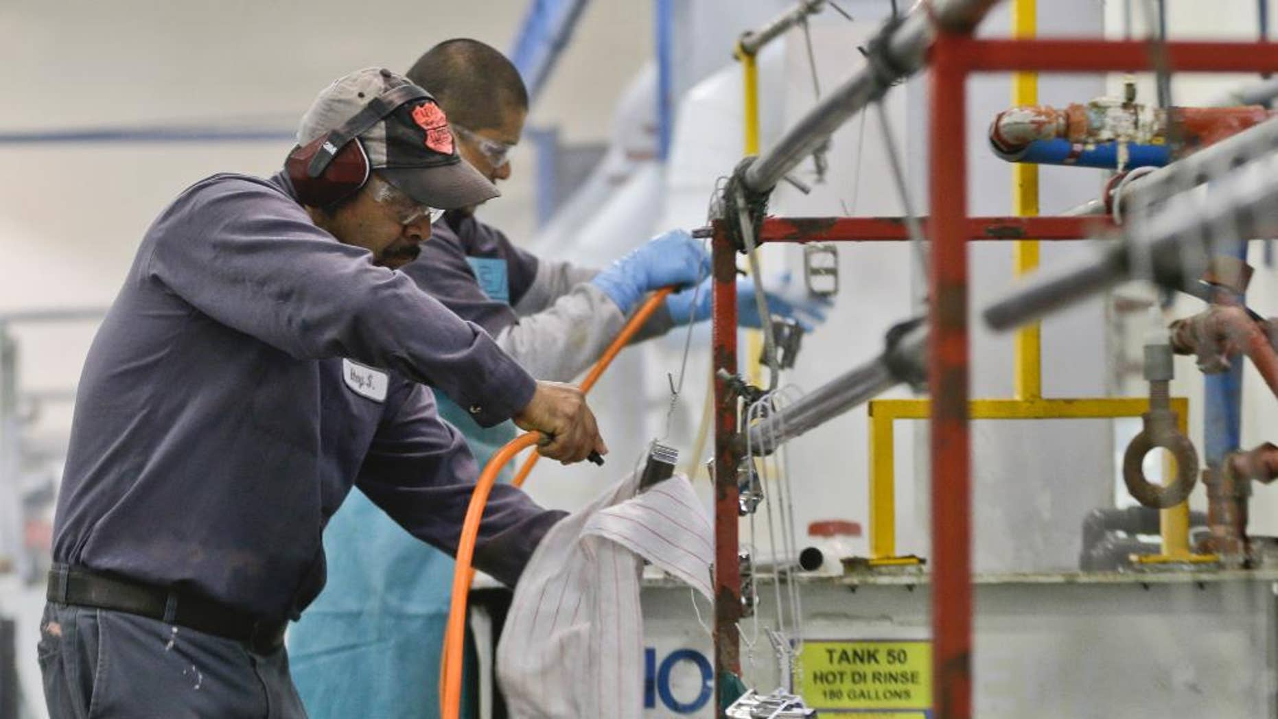 FILE - In this Thursday, Oct. 10, 2013, file photo, employees at Sheffield Platers Inc. work on the factory floor in San Diego. The labor Department releases fourth-quarter productivity data on Thursday, March, 6, 2014. (AP Photo/Lenny Ignelzi, File)