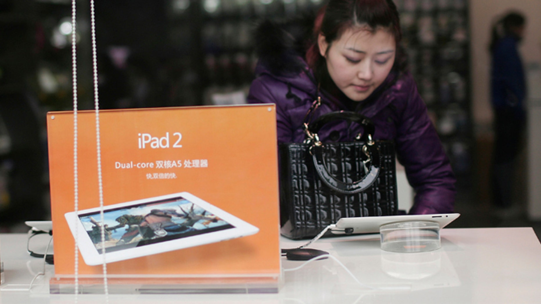 Feb. 27, 2012: A customer tries out Apple's iPad 2 at a retail shop in Chongqing, China. The Taiwan-based maker Proview Electronics said Monday it is now seeking to regain worldwide rights to the iPad name and is suing Apple Inc. for alleged fraud and unfair competition.
