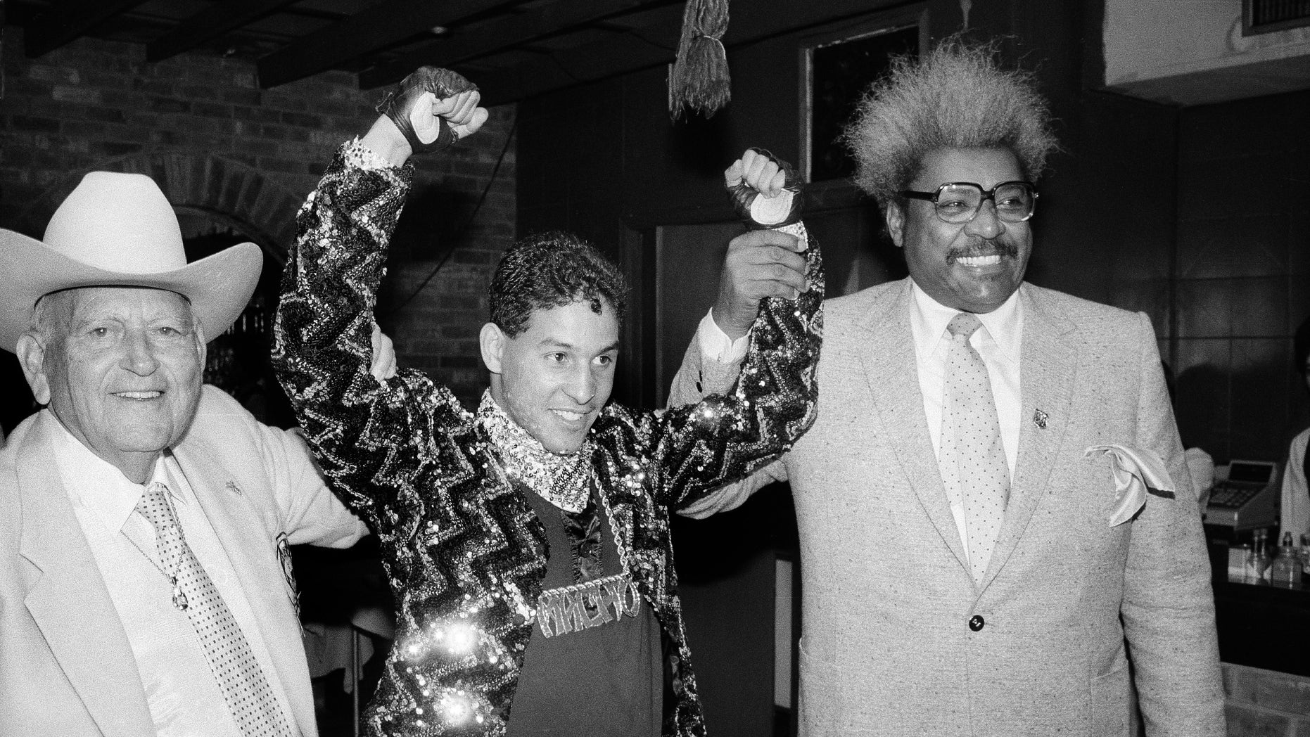 """In this Dec. 9, 1986 file photo, Hector """"Macho"""" Camacho WBC lightweight boxing champion, is escorted by Marty Cohen, left, and boxing promoter Don King, right, during a news conference in New York."""