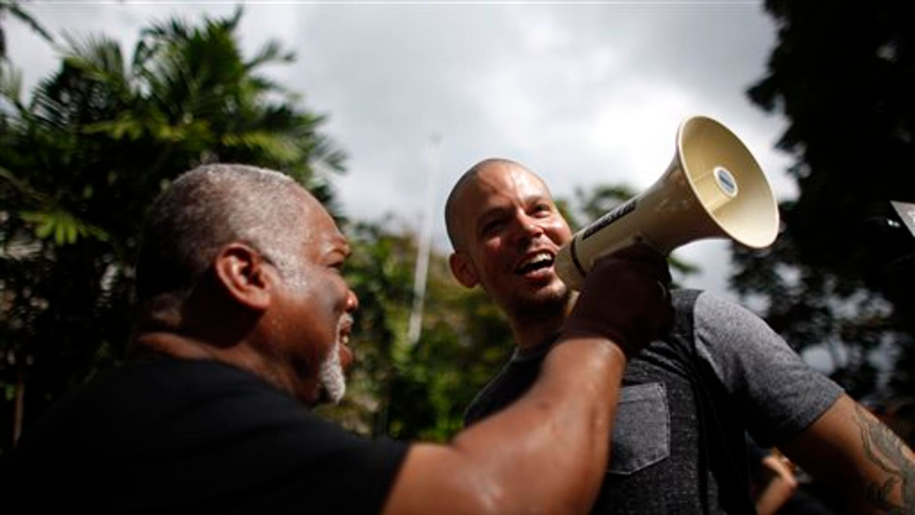 """Striking teacher Jose Iturbe, left, holds up the megaphone to entertainer Rene Perez Joglar, also known as """"Residente"""" from Puerto Rico's musical group Calle 13, who joined the protest by striking teachers outside a public school in San Juan, Puerto Rico, Tuesday, Jan. 14, 2014. Hundreds of teachers across Puerto Rico walked off their jobs in a two-day strike over cuts to their pensions that the island's government says are necessary to avert financial disaster but that educators say will force many of them into poverty. (AP Photo/Ricardo Arduengo)"""